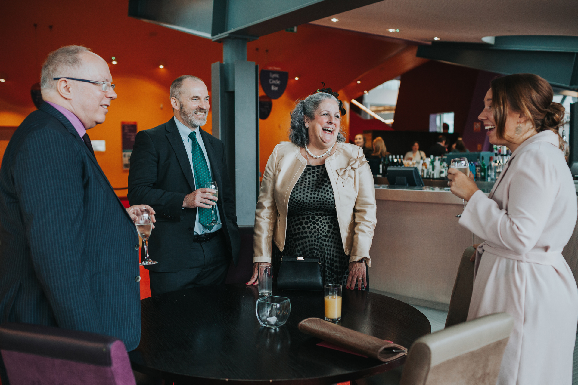 Four Wedding Guests Laugh together.