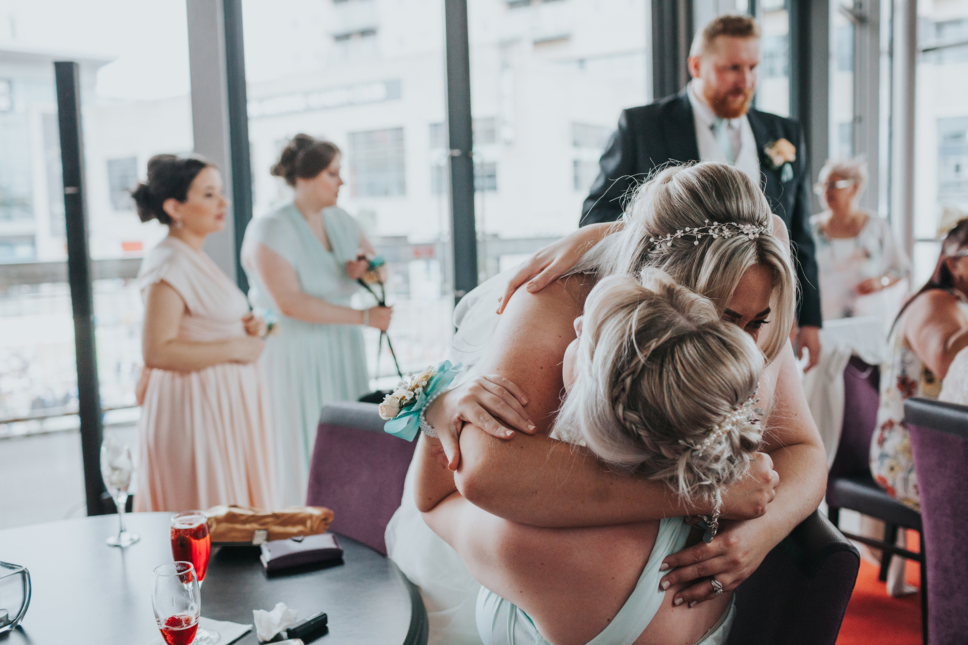 Bride hugs another bridesmaid.