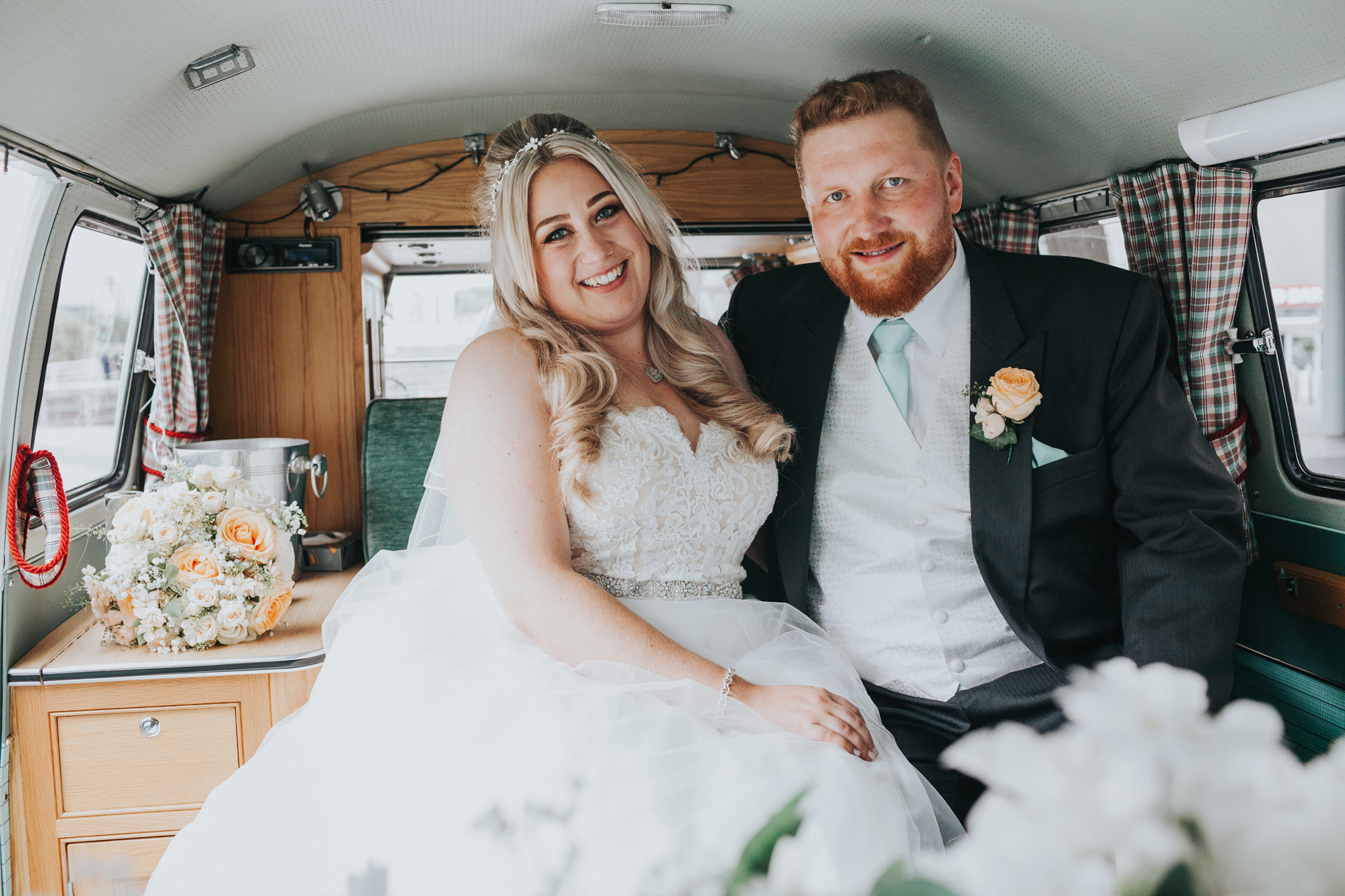 Bride and Groom sit in their camper van.