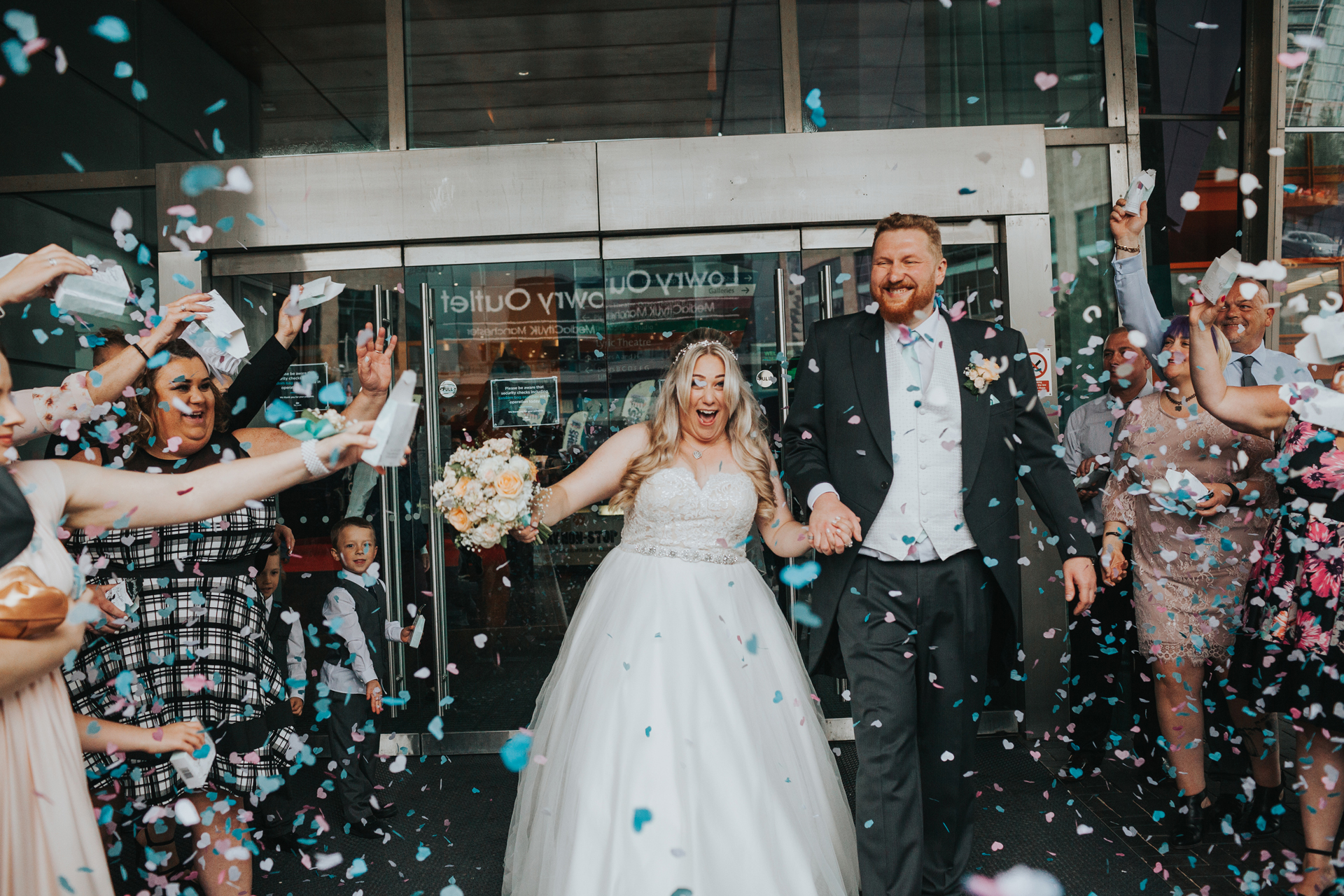 Bride and Groom exit the Lowry Theatre to have confetti thrown at them by wedding guests.