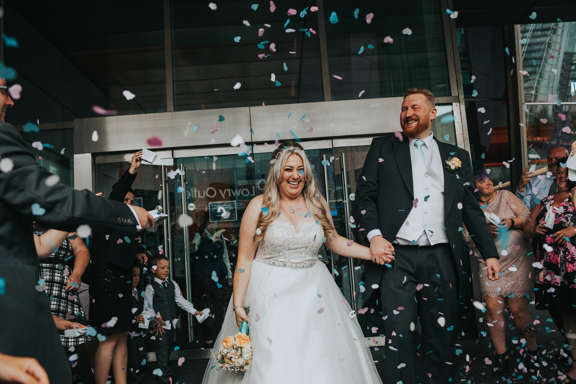 Bride and Groom Laugh as they have confetti thrown at them.
