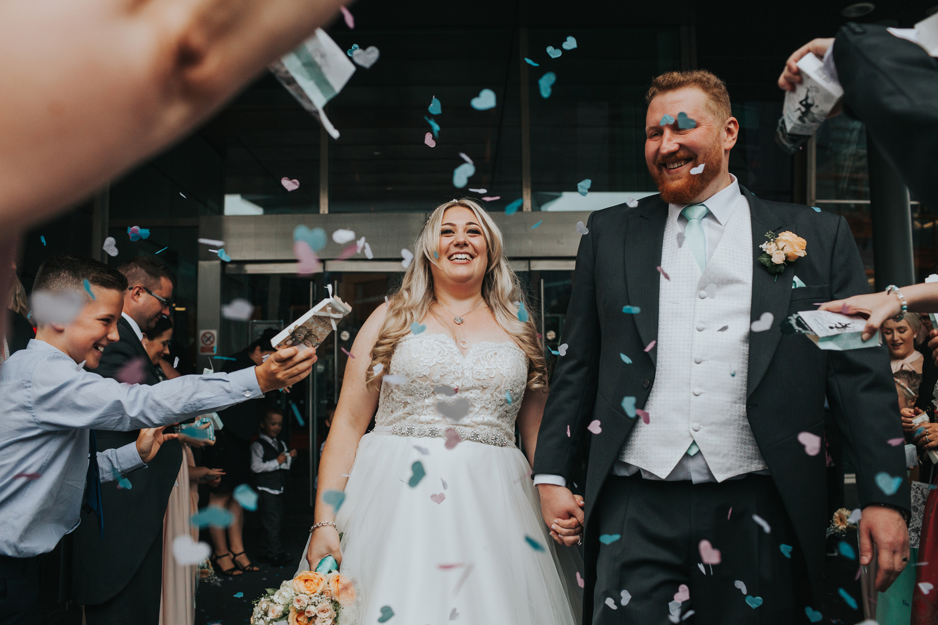 Bride and Groom look happy as they have confetti thrown at them from all angles.