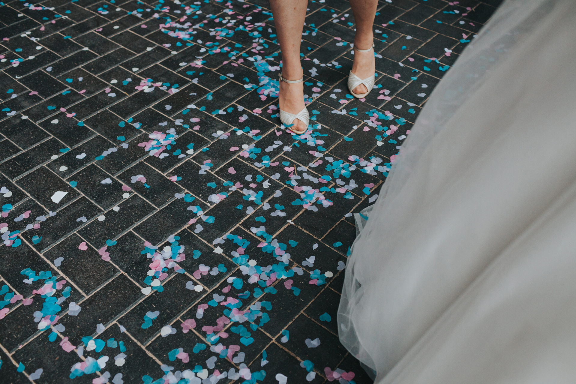 The floor is covered in pink and teal confetti.