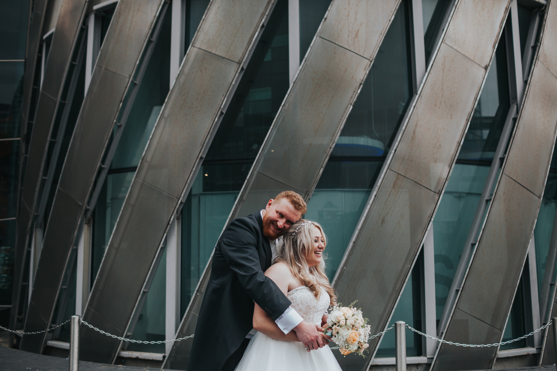 Colour photo of groom hugging bride from behind.