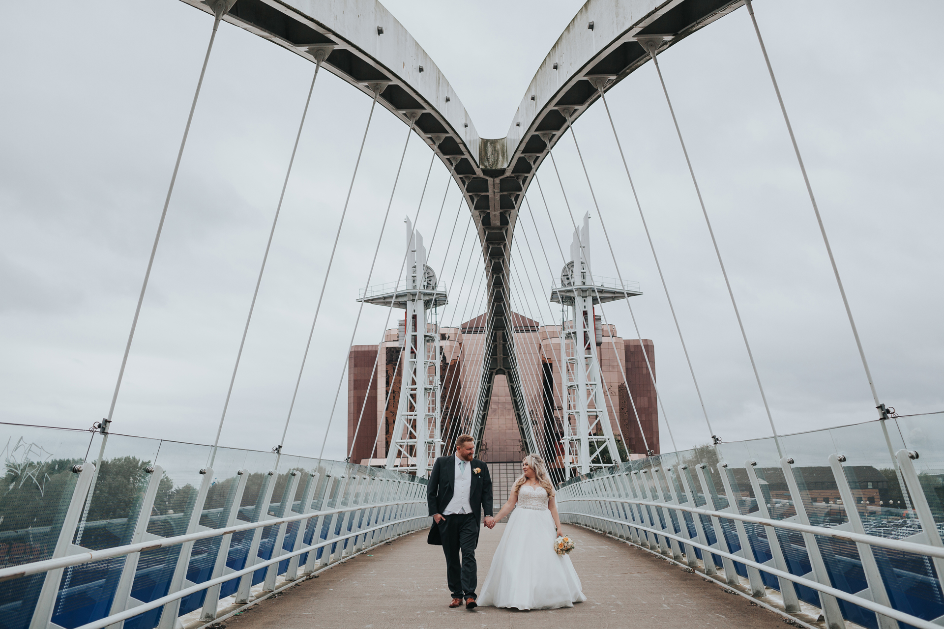 Bride and groom walk down the bridge together.