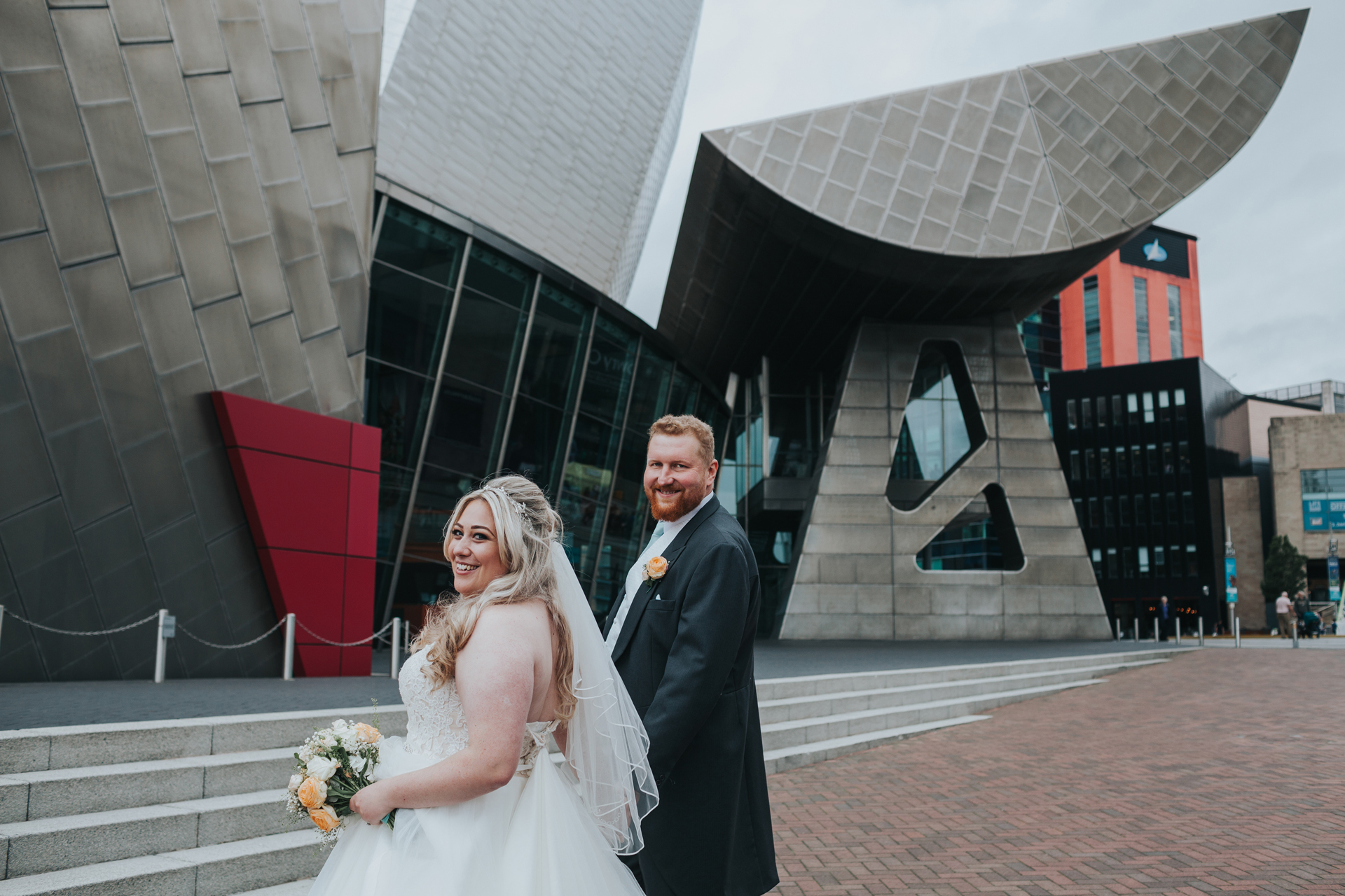 Bride and Groom stand in front on The Lowry Theatre.