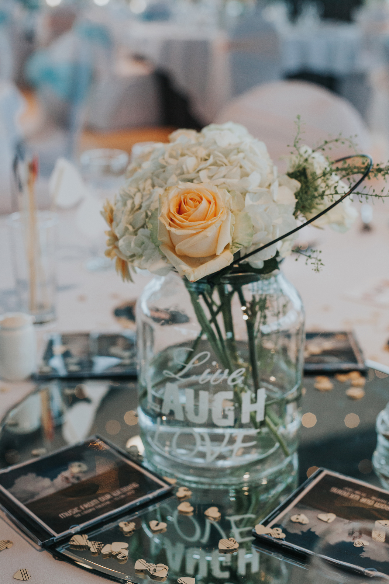 Roses in glass jars on the wedding table.