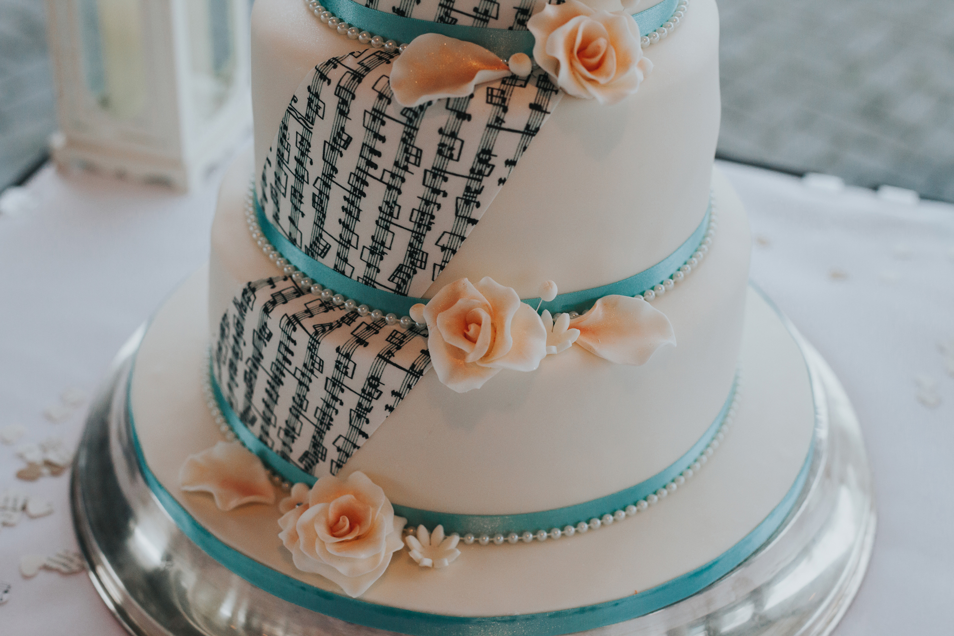 Wedding cake with sheet music and peach rose detail.