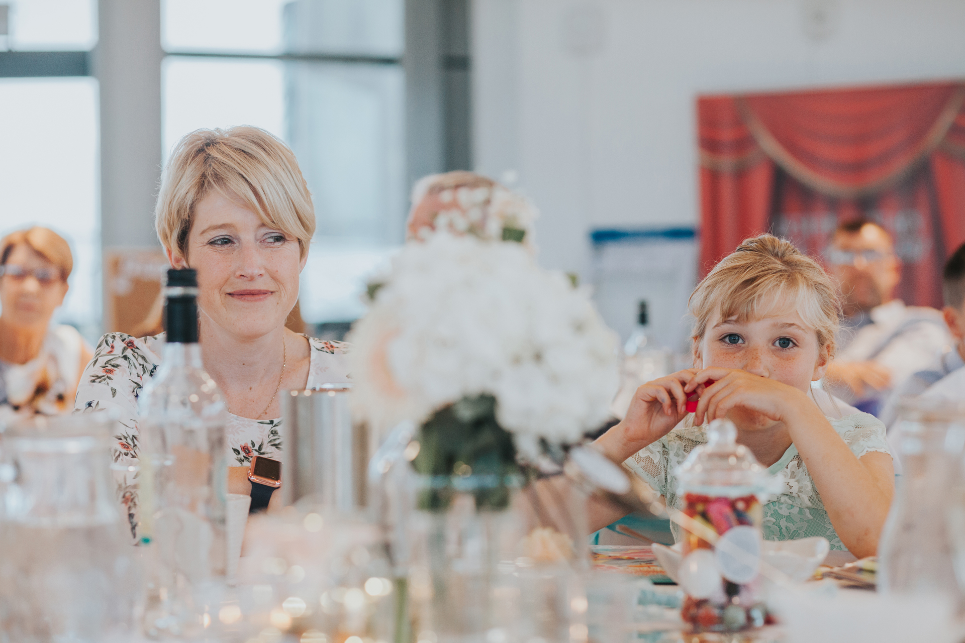 Flower girl eats sweets at wedding table.