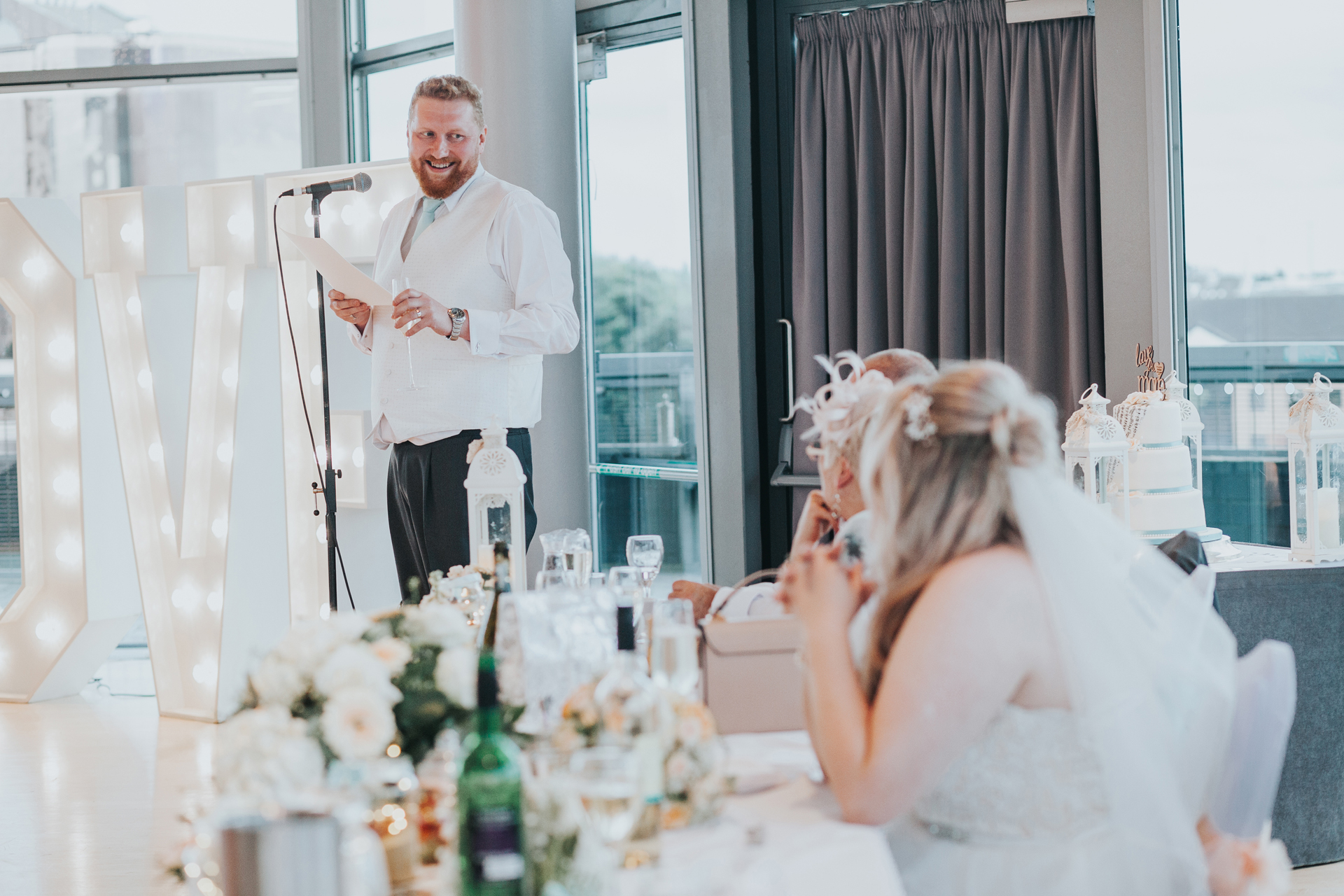 Groom looks on at his bride while giving his speech.