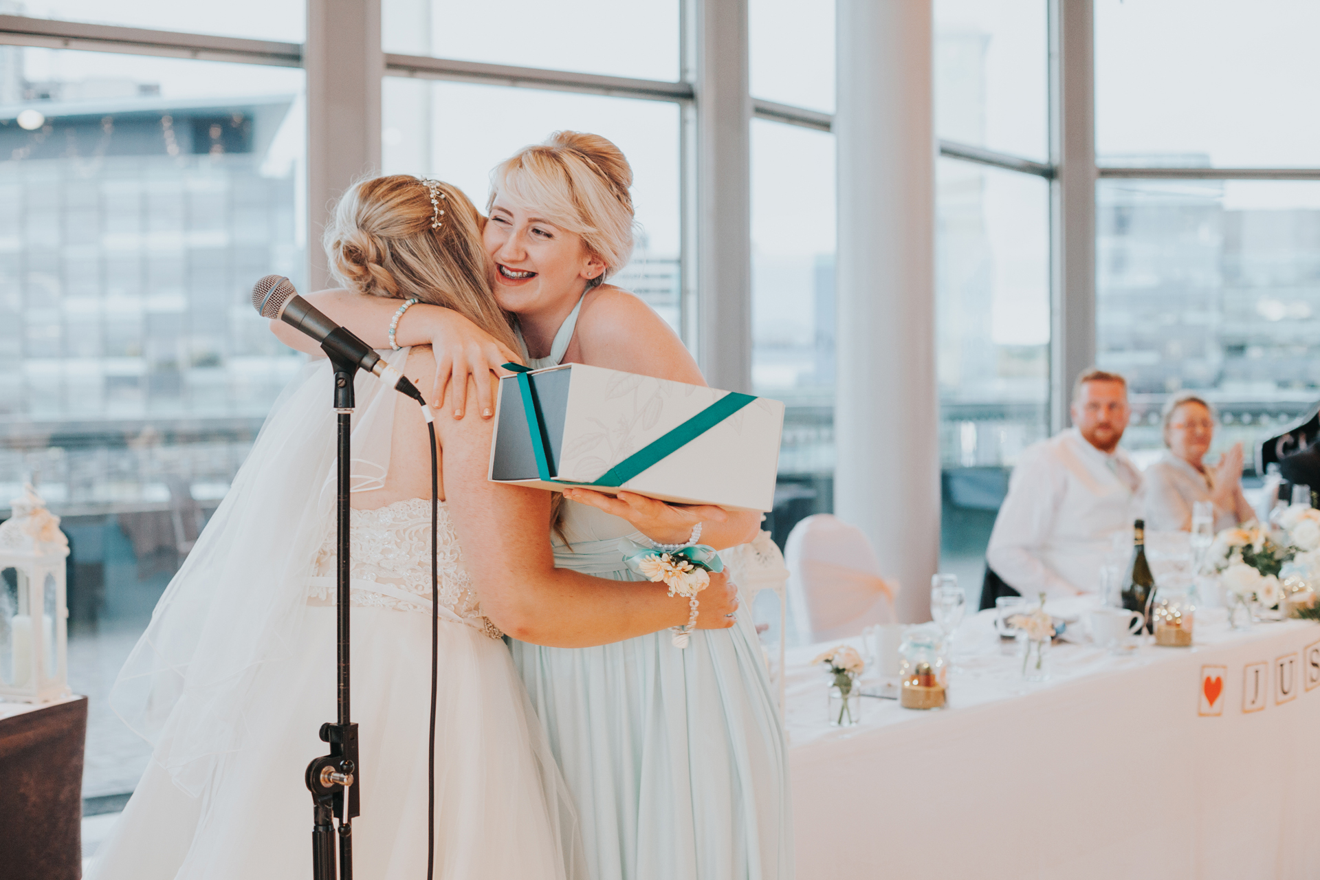Bridesmaid gives bride a big hug.