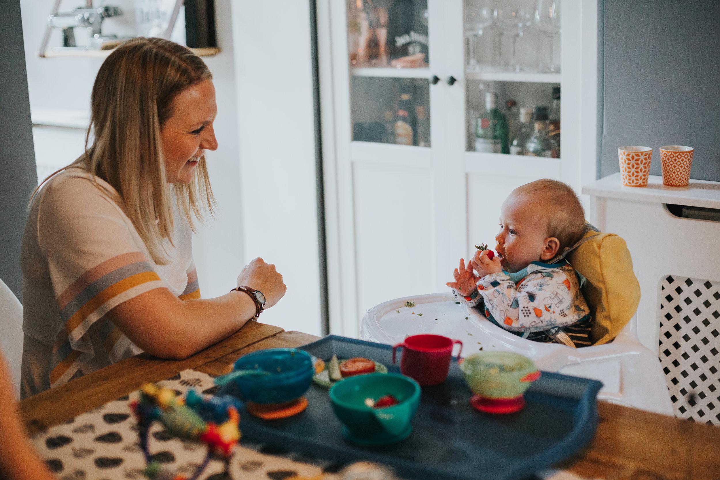 Mum watches baby eating smiling.