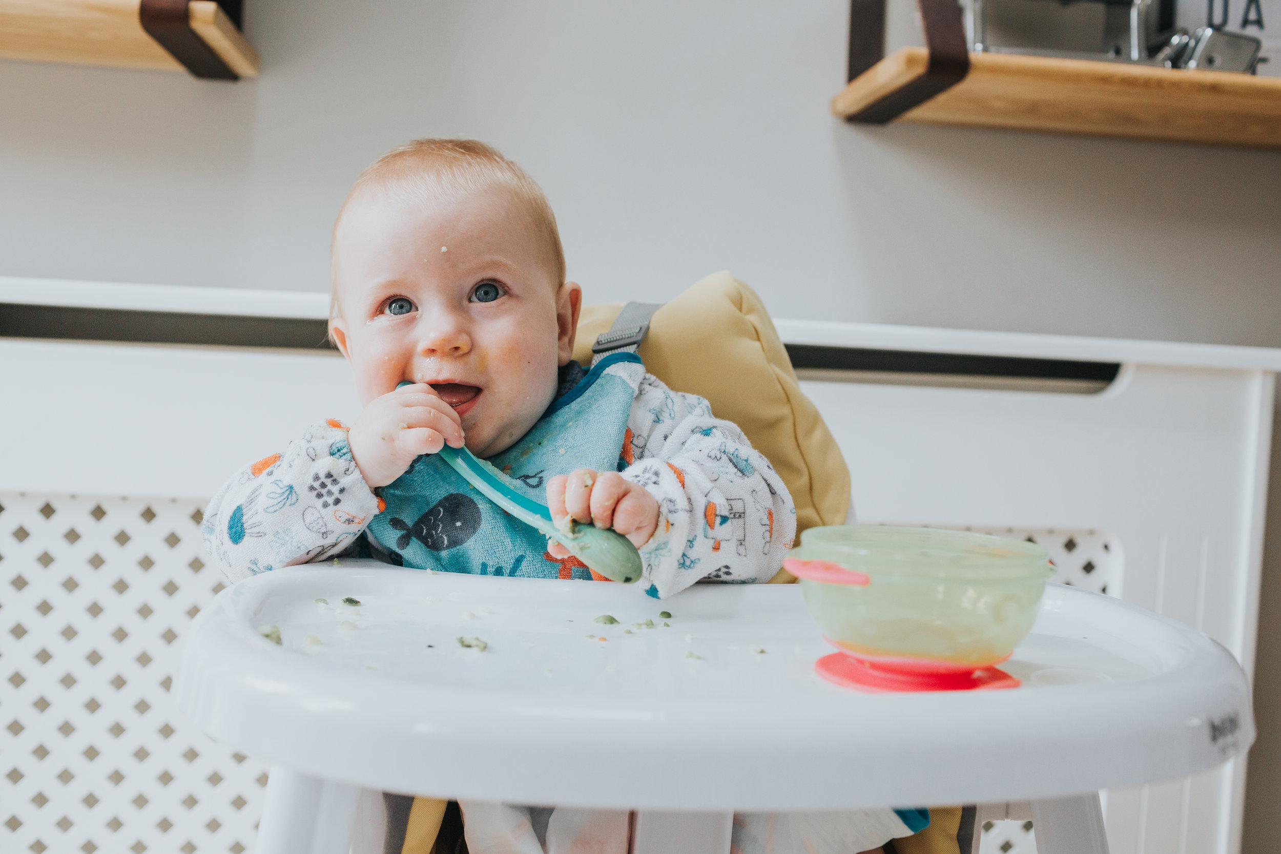 Baby smiles while holding spoon in her mouth.