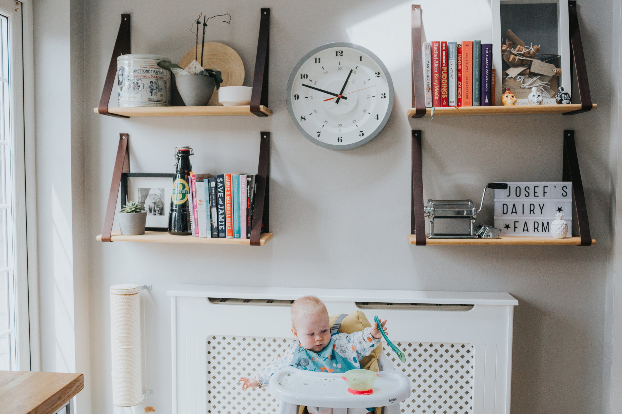 Baby playing with spoon in his high chair below a large clock.