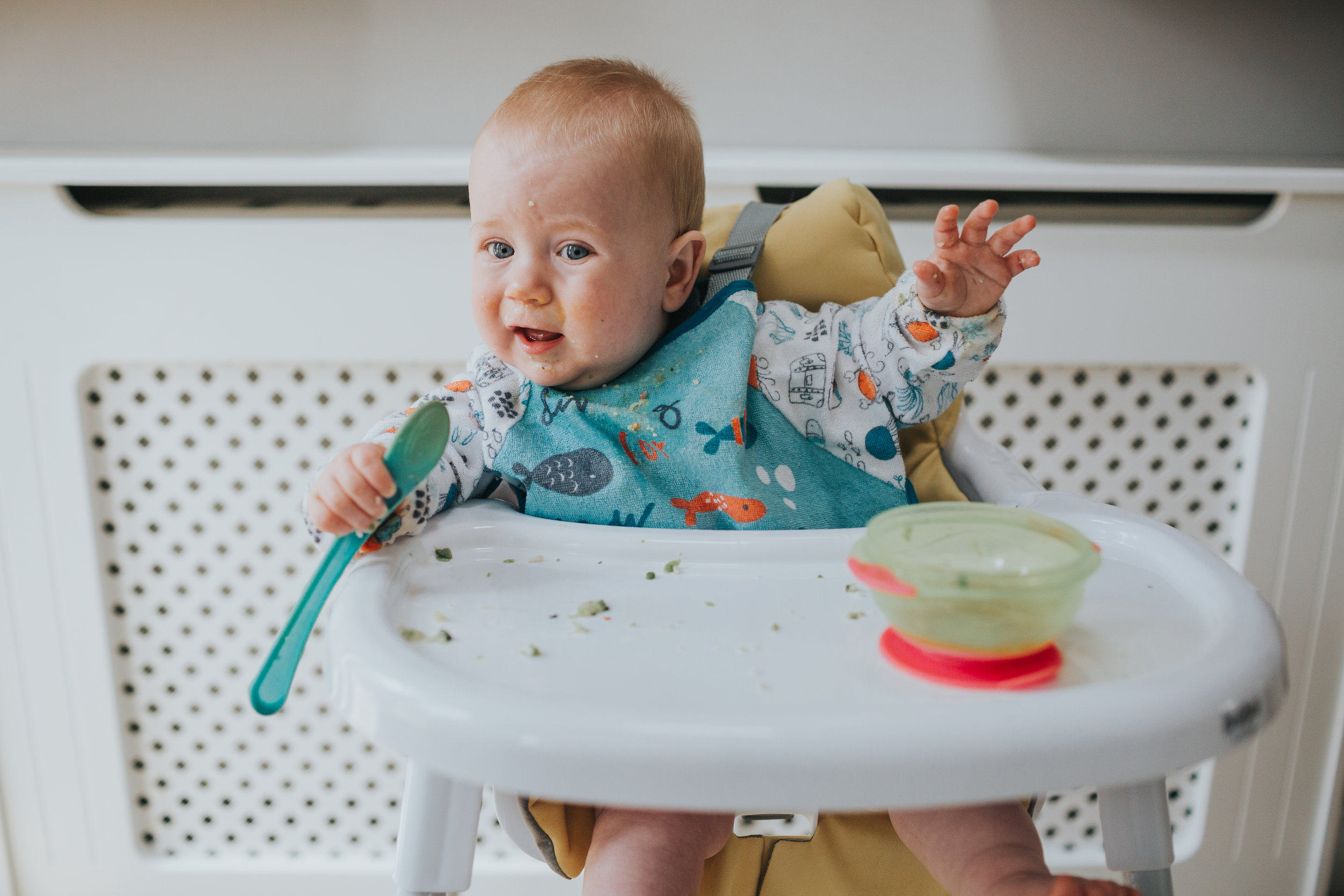 Baby uses his spoon as a microphone.