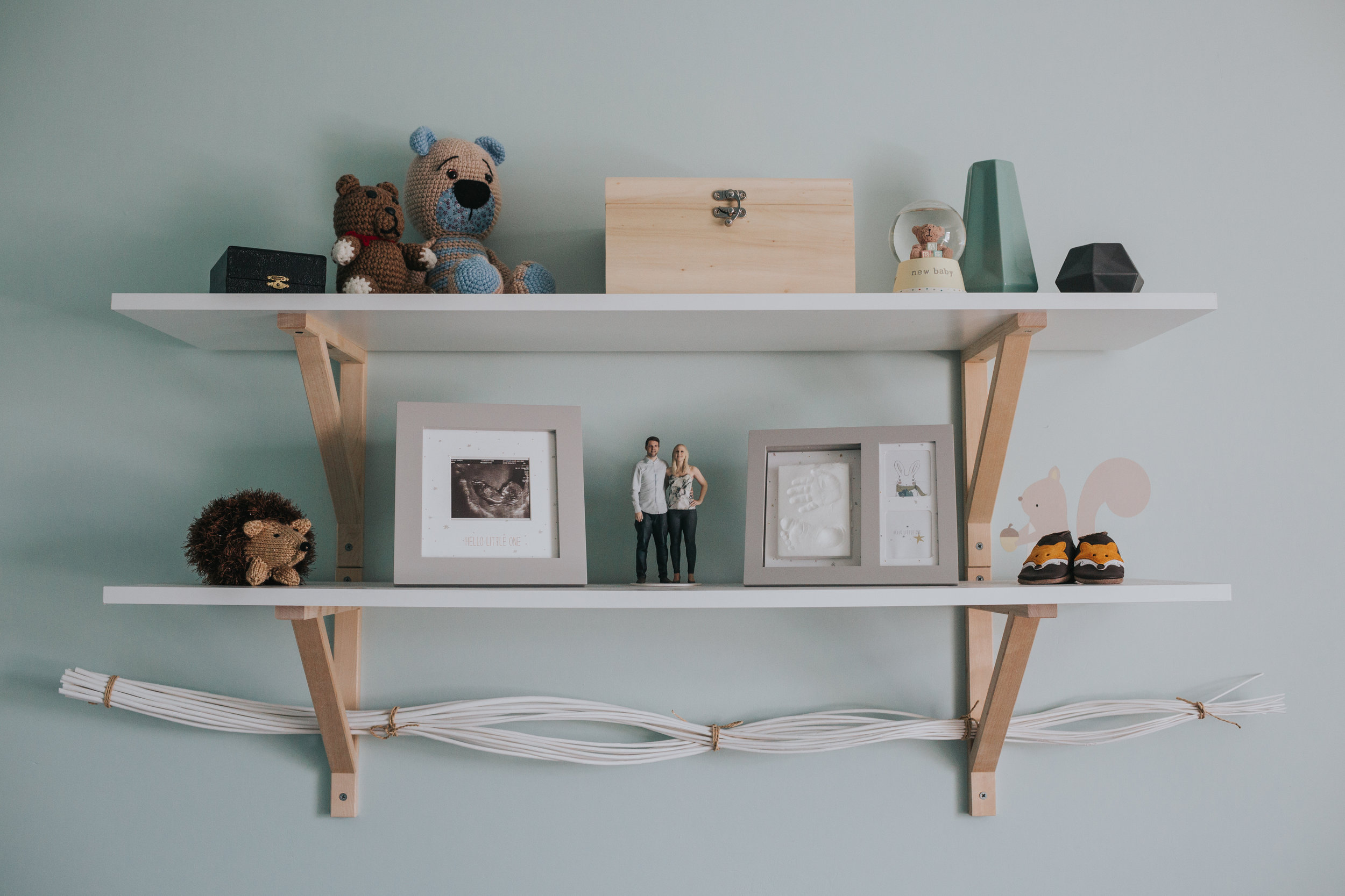Shelves in babies room with photos and toys.