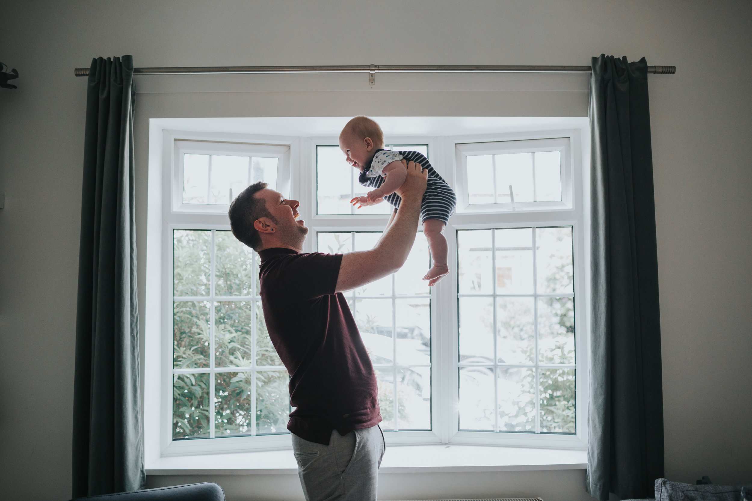 Dad chucks baby up and down in font of window to celebrate.