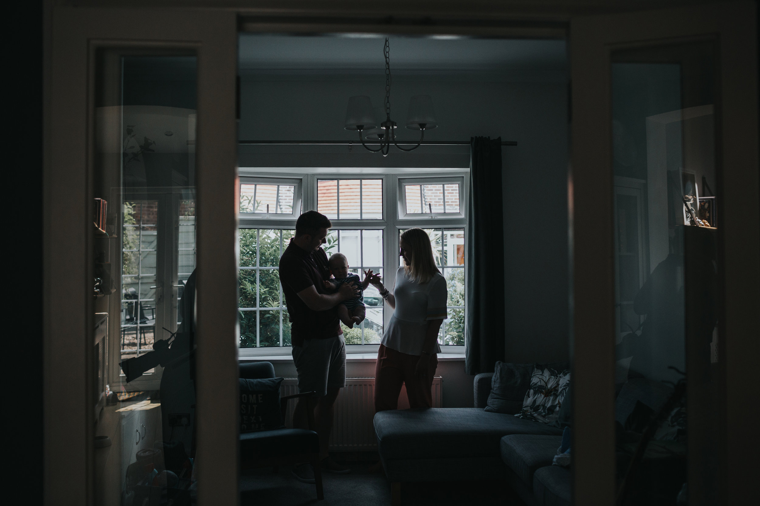 Silhouette of family in front of living room window.