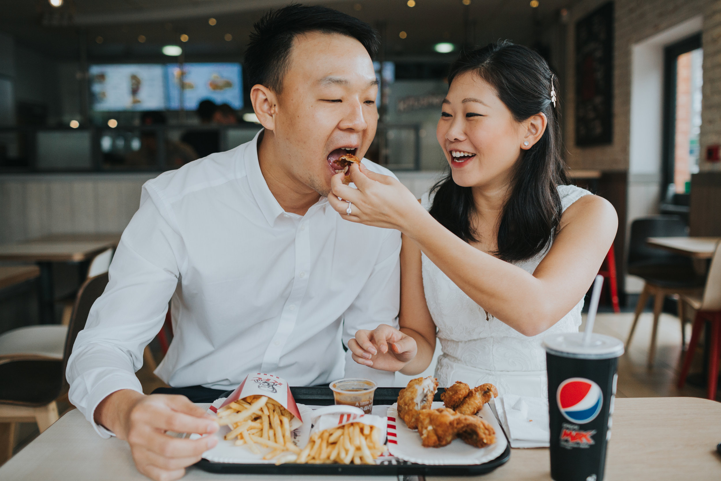Couple feed each other chicken in KFC.