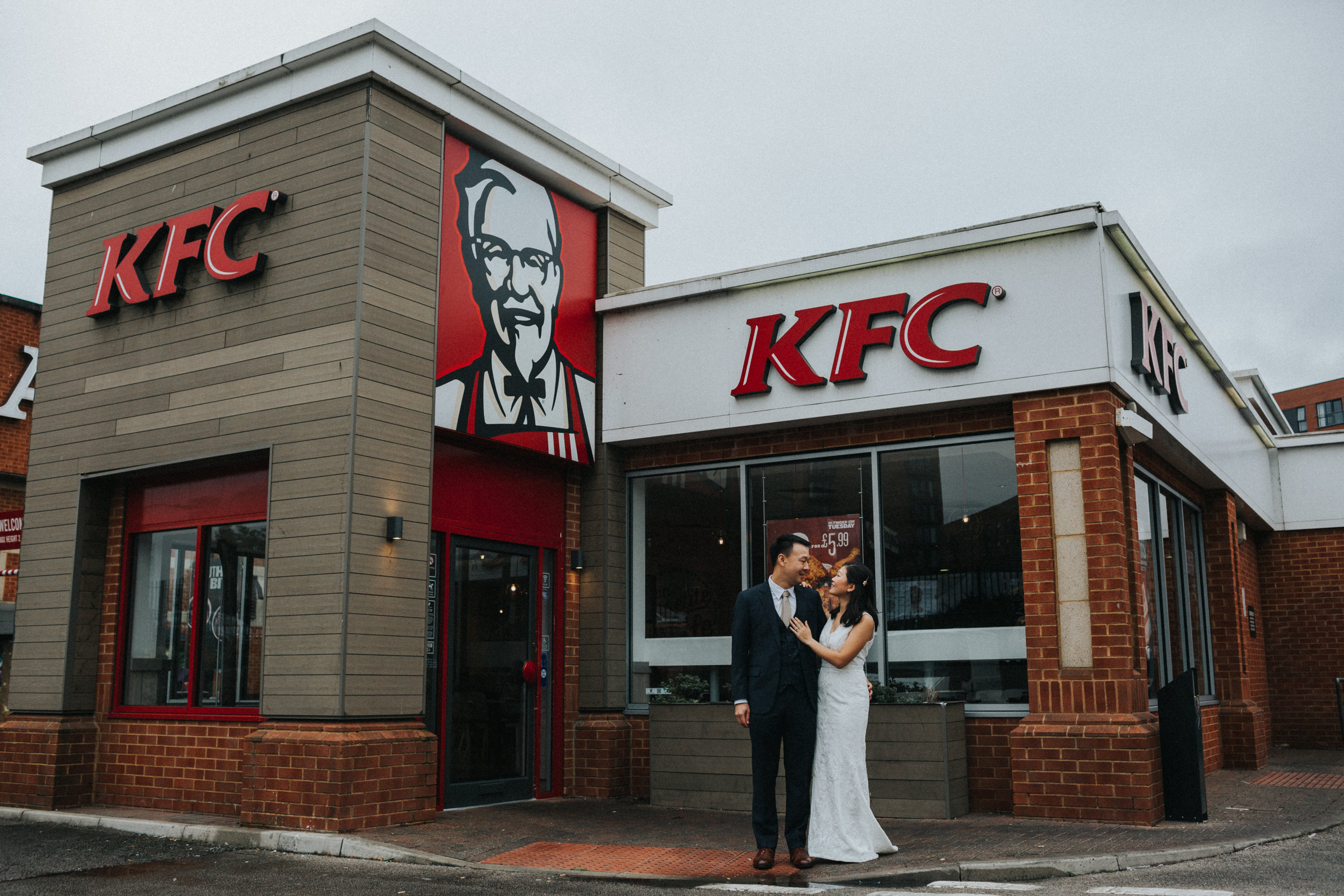 Couple embrace outside KFC.