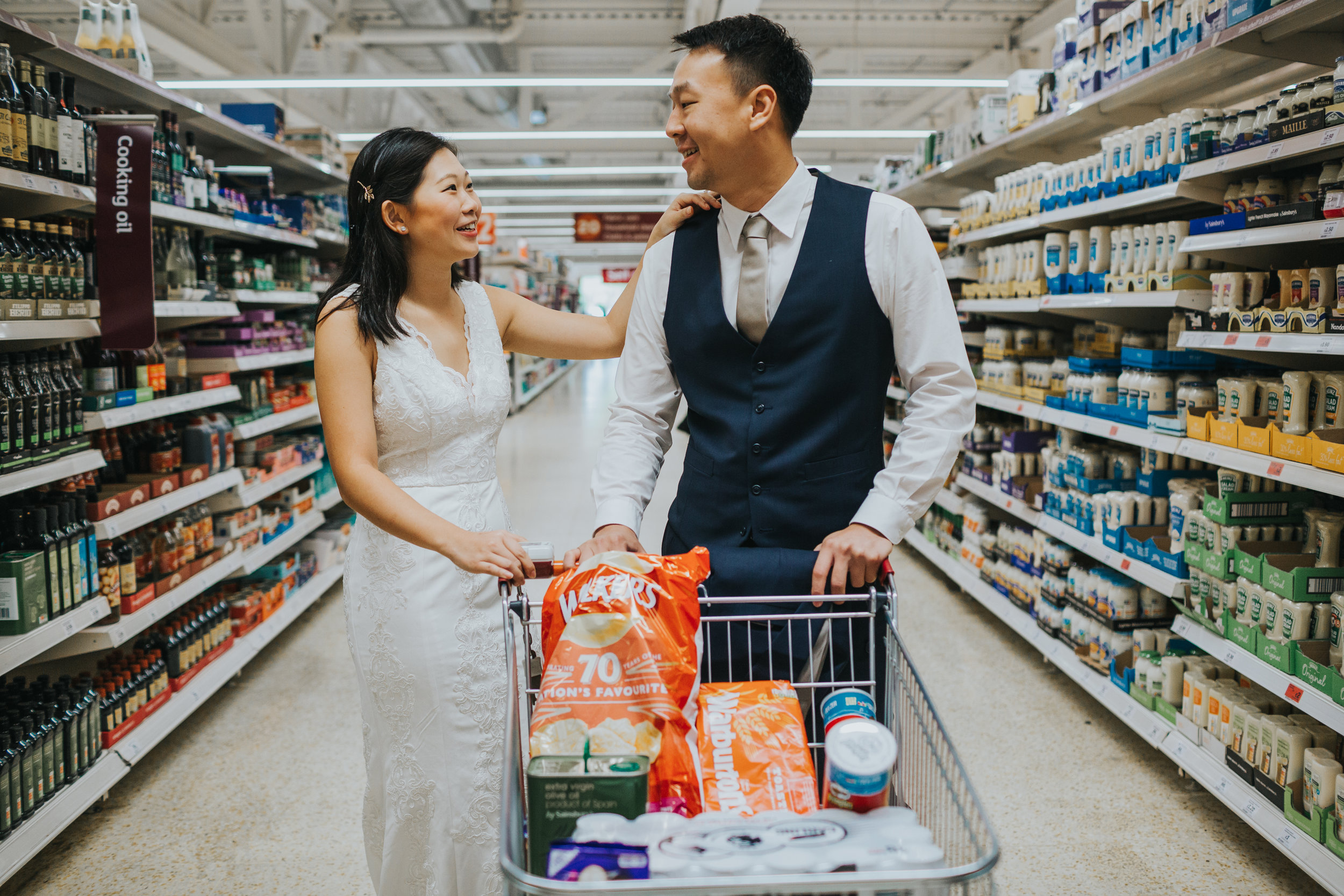 Couple pause together with shopping trolly in supermarket, Manchester.