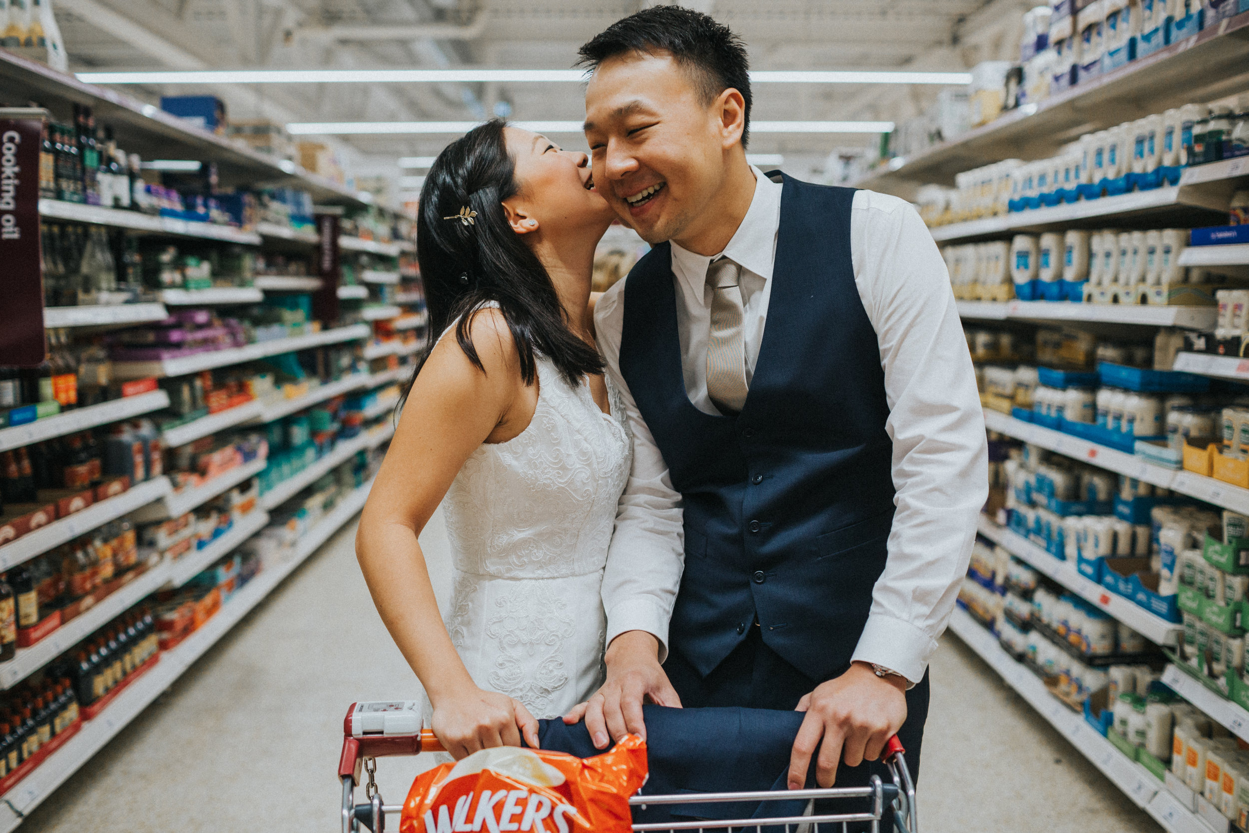 Bride whispers into grooms ear in supermarket.