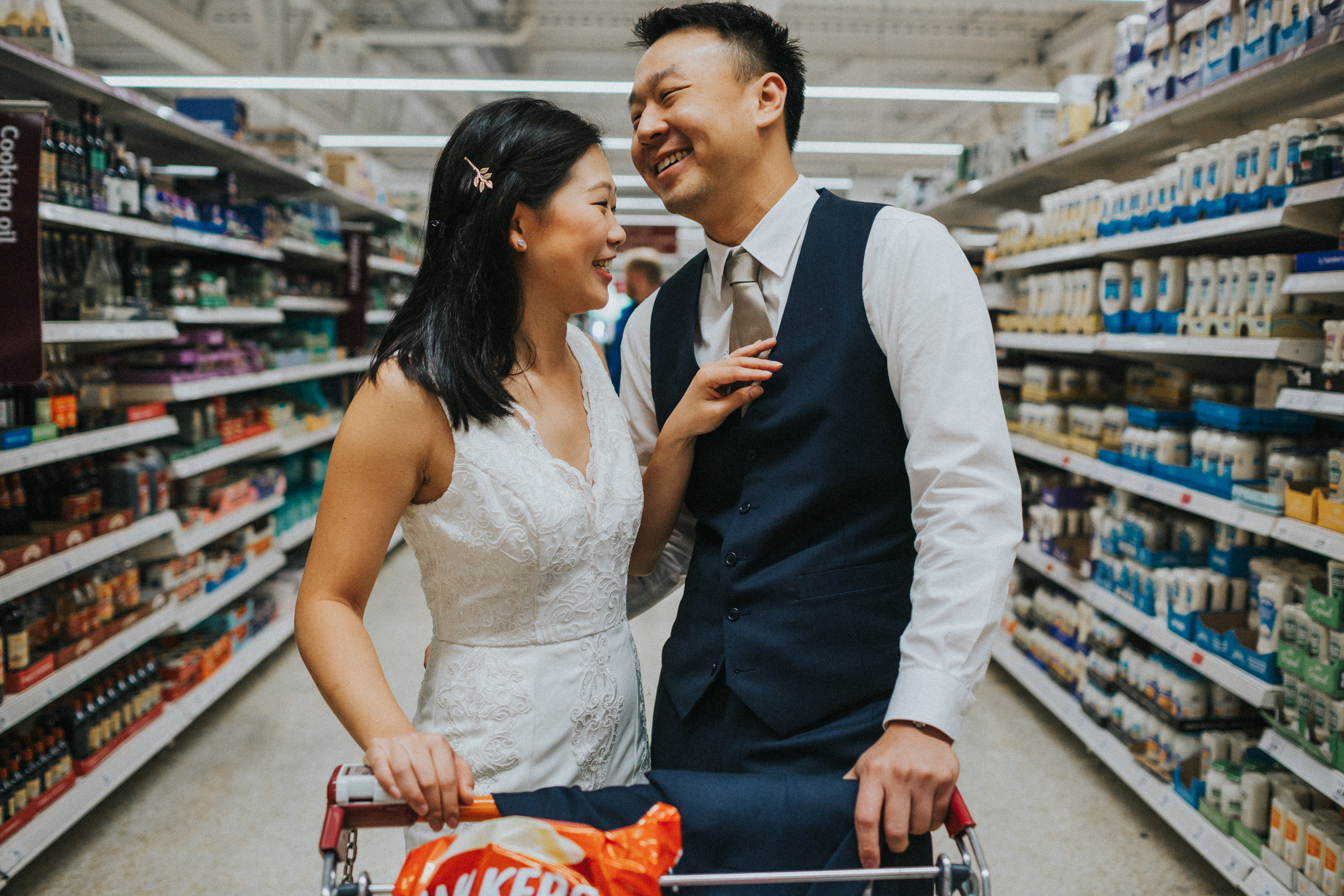 Bride fixing Grooms tie in supermarket.