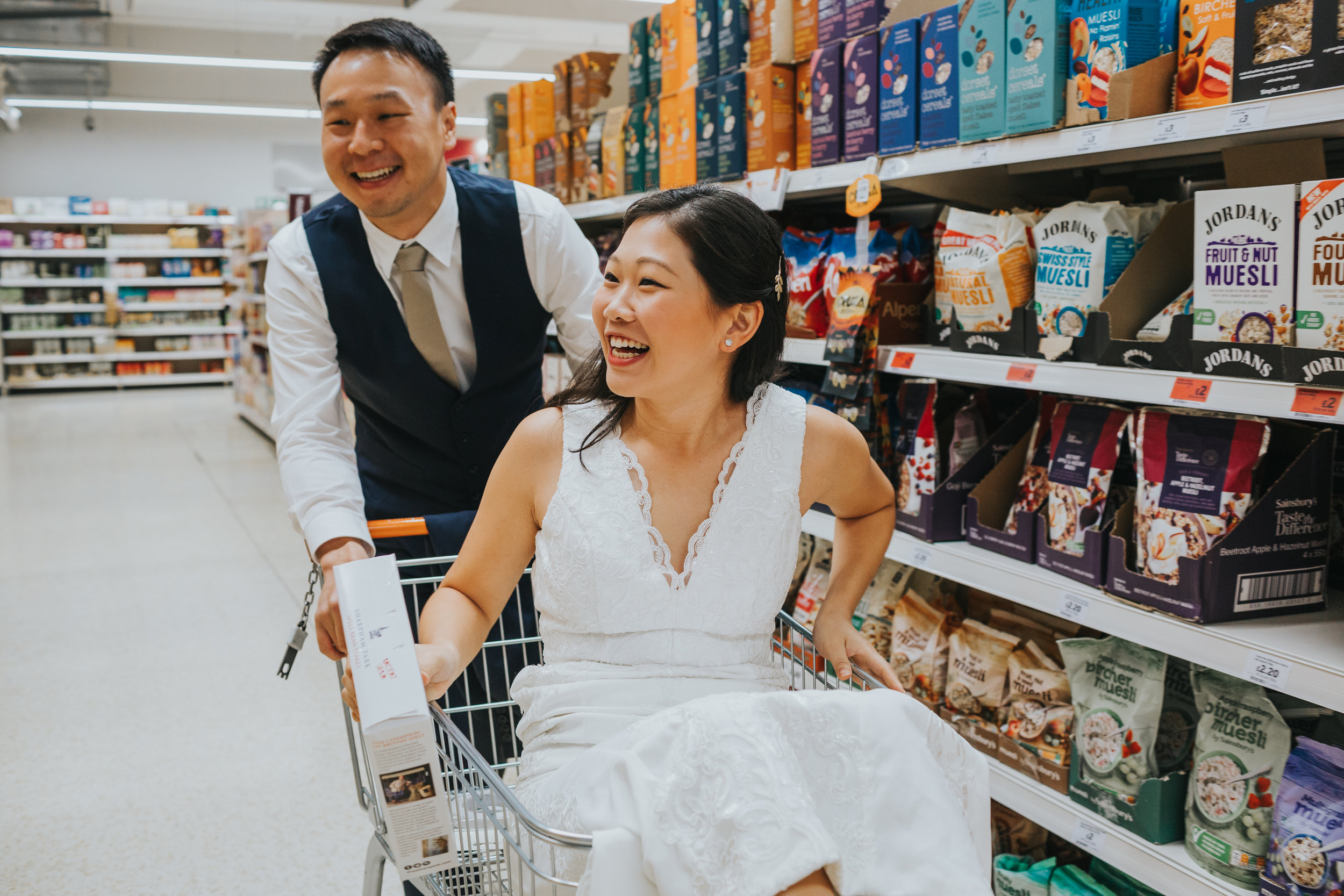 Groom pushes bride down the aisle in shopping trolley.