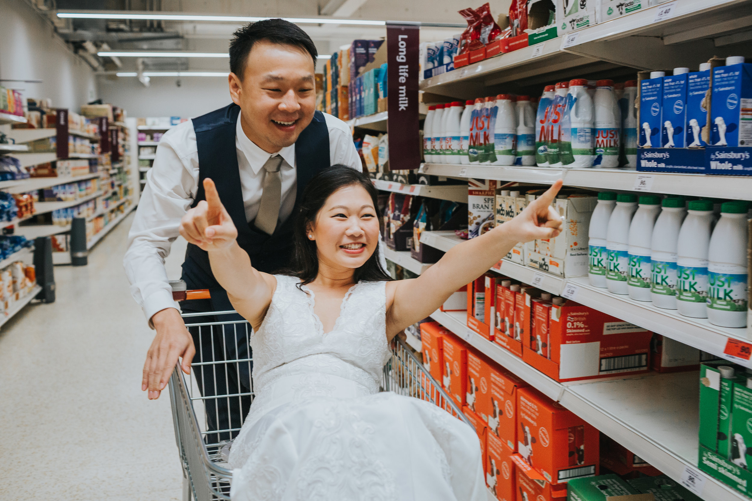 Bride poses in rock and roll pose as Groom pushes her down the aisle in shopping trolley.