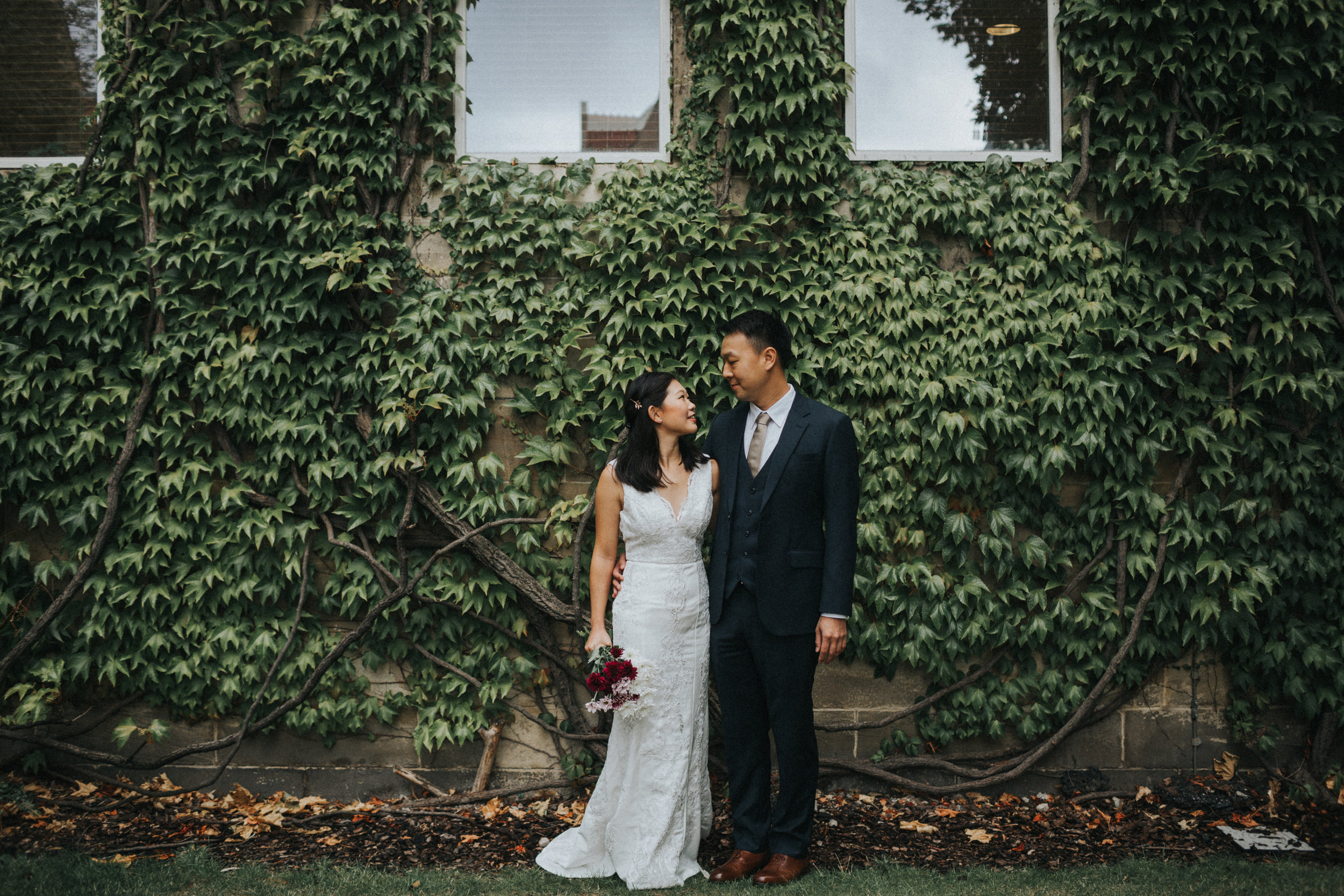 Couple stand together in front of a wall full of Ivy at Manchester University.