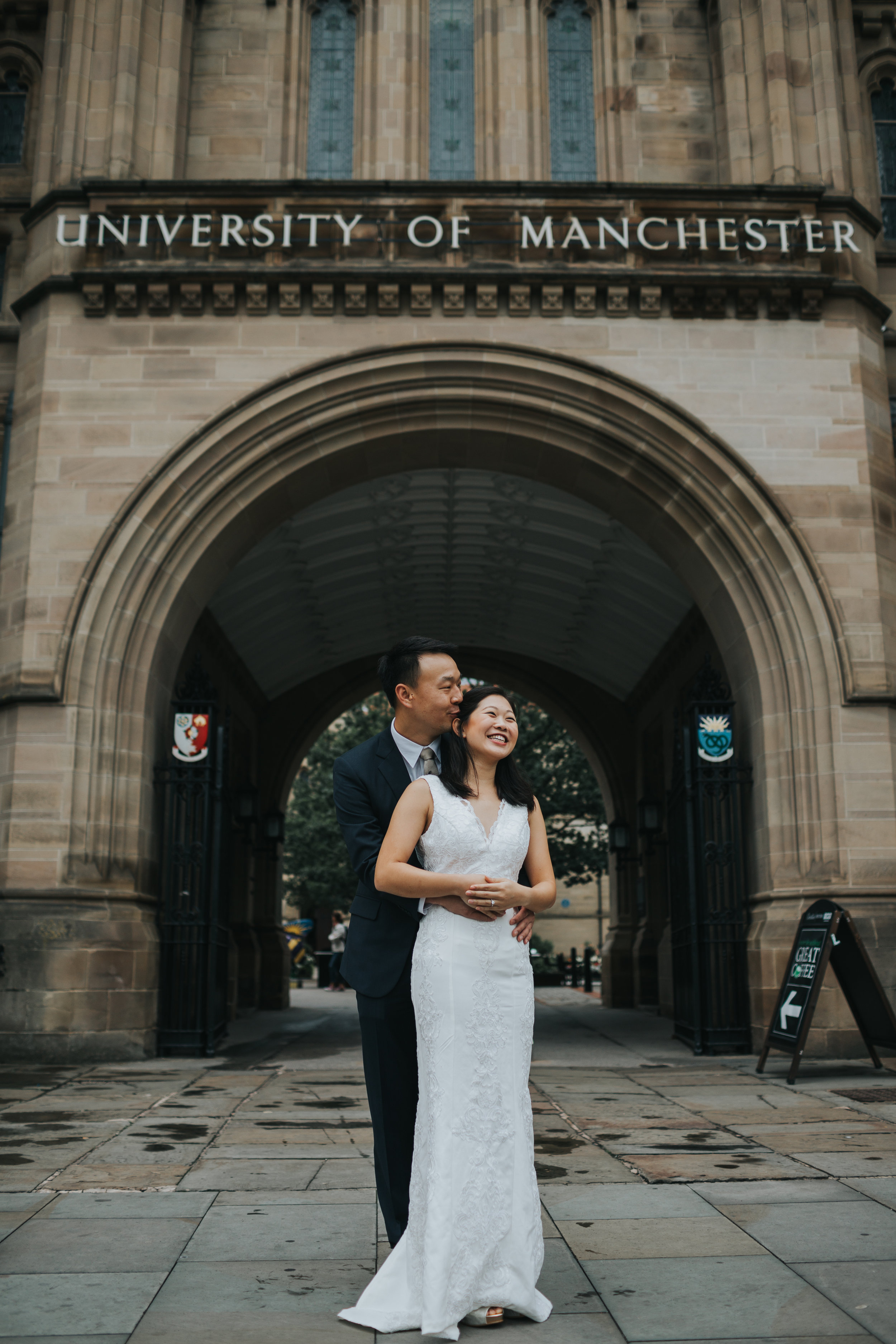 Couple have a cuddle in the Manchester university archway.