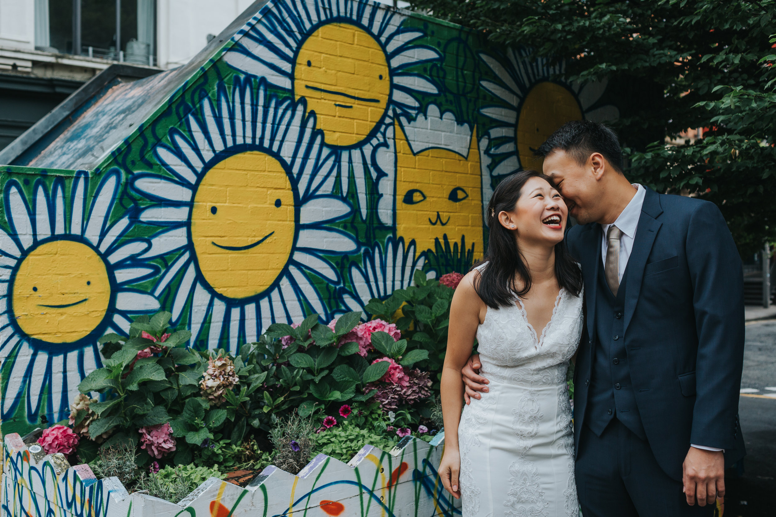 Couple laughing together in front of sunshine graffiti in Manchester's Northern Quarter.