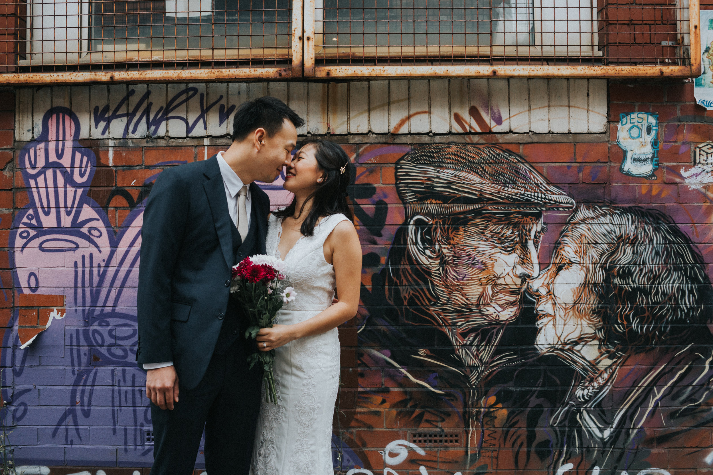 Couple give each other an eskimo kiss in front of old couple graffiti.