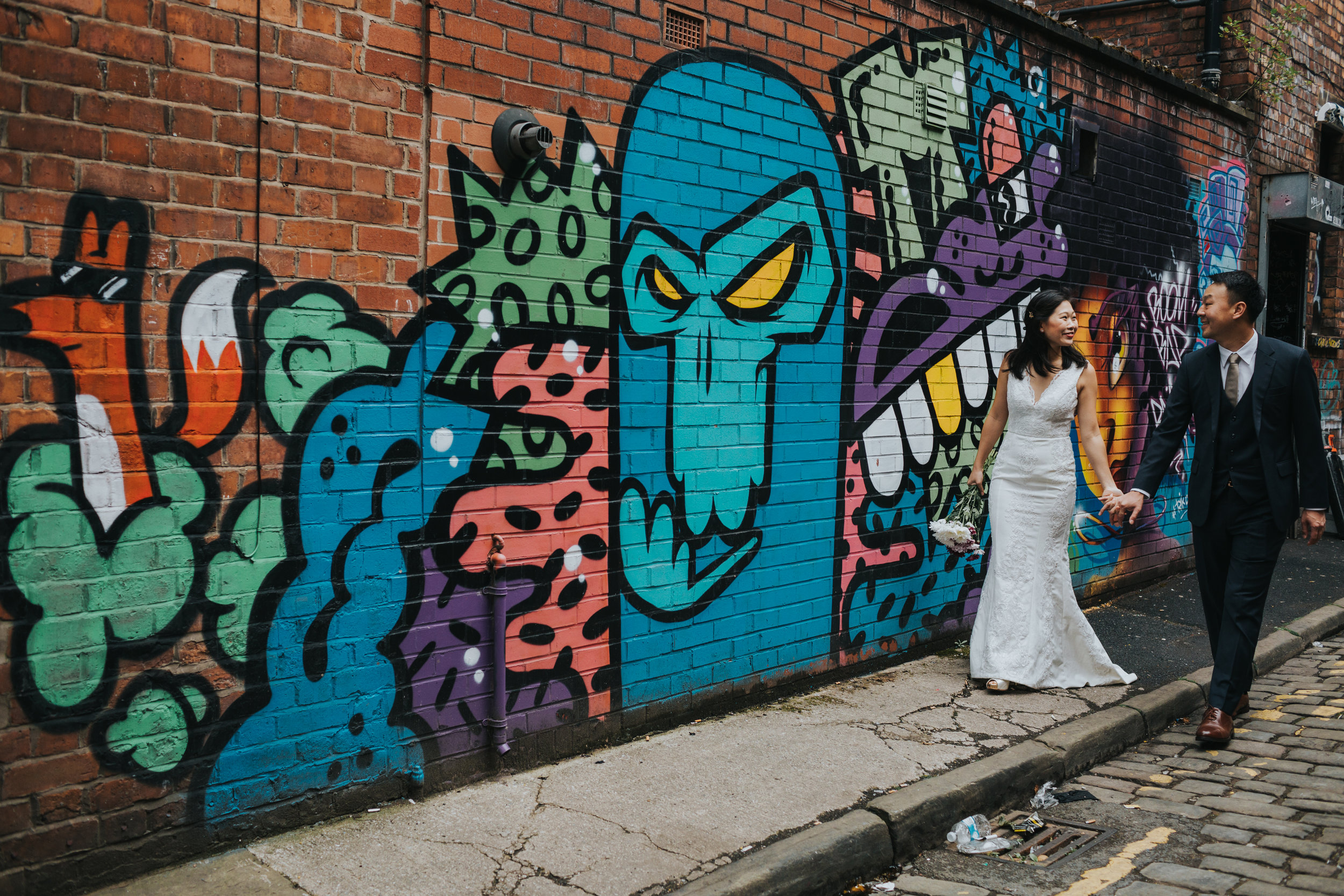 Couple walk along colourful graffiti.