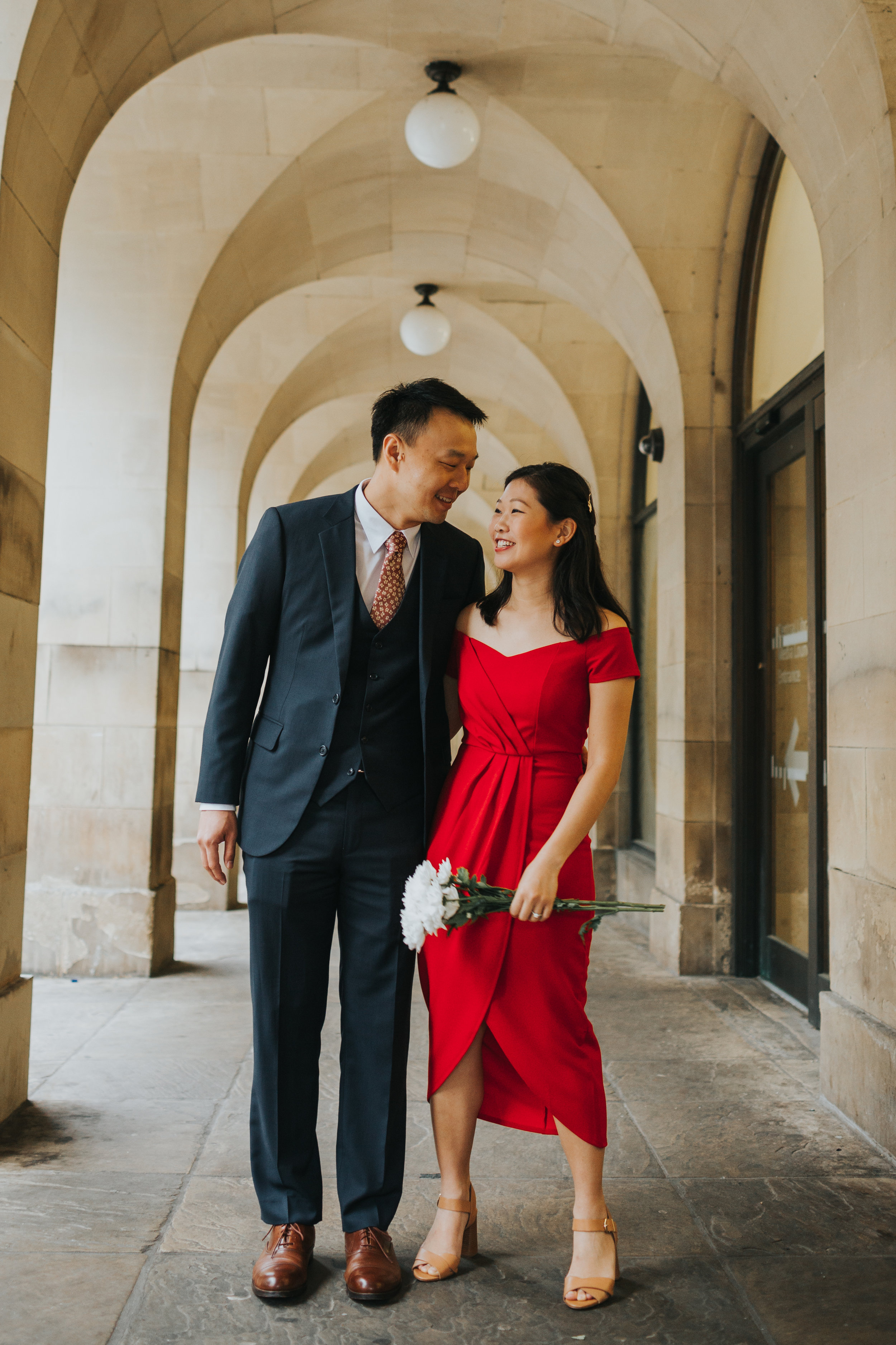 Couple smiling under the Manchester Town Hall Archways.