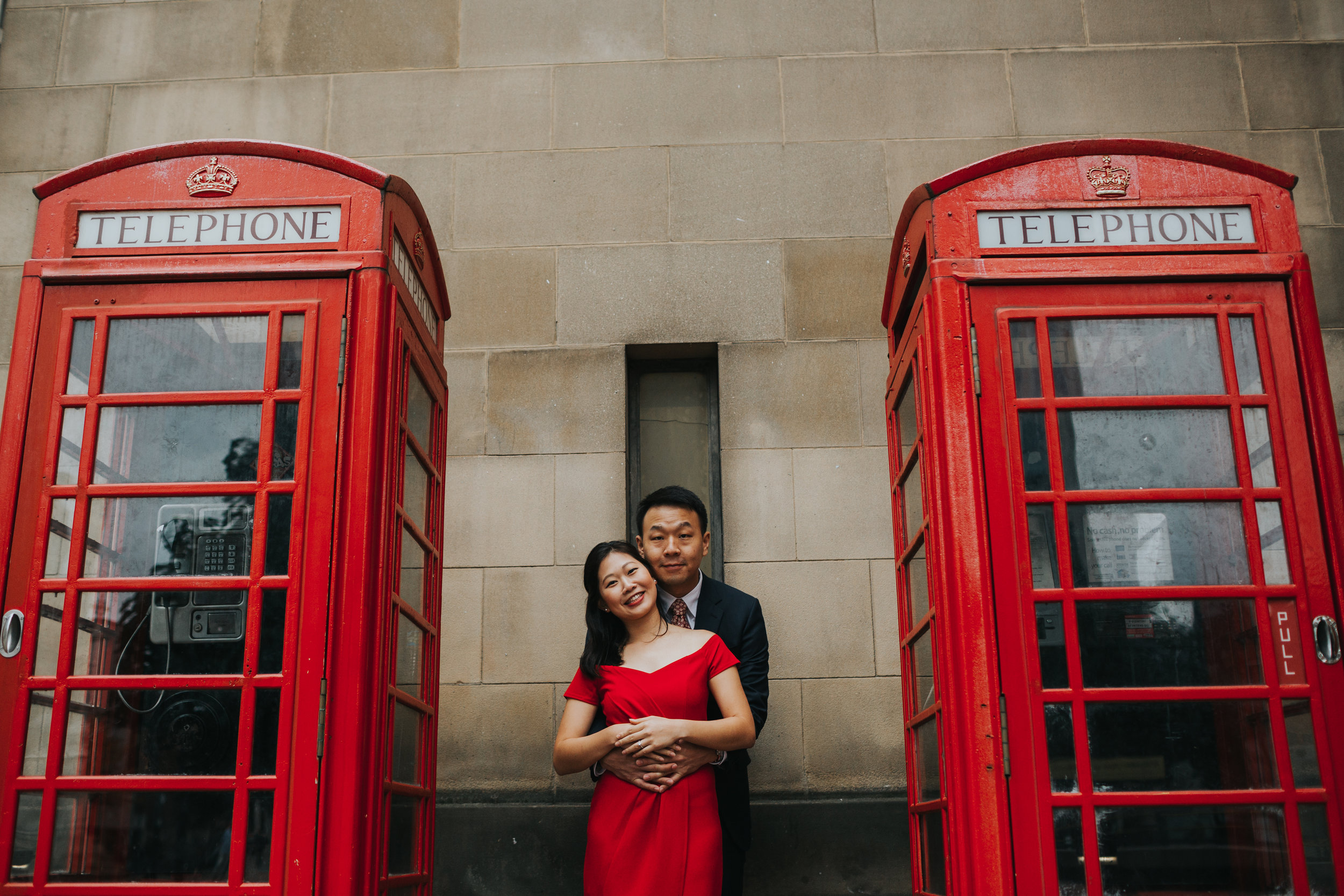 Couple cuddle in between two red phone boxes Manchester.