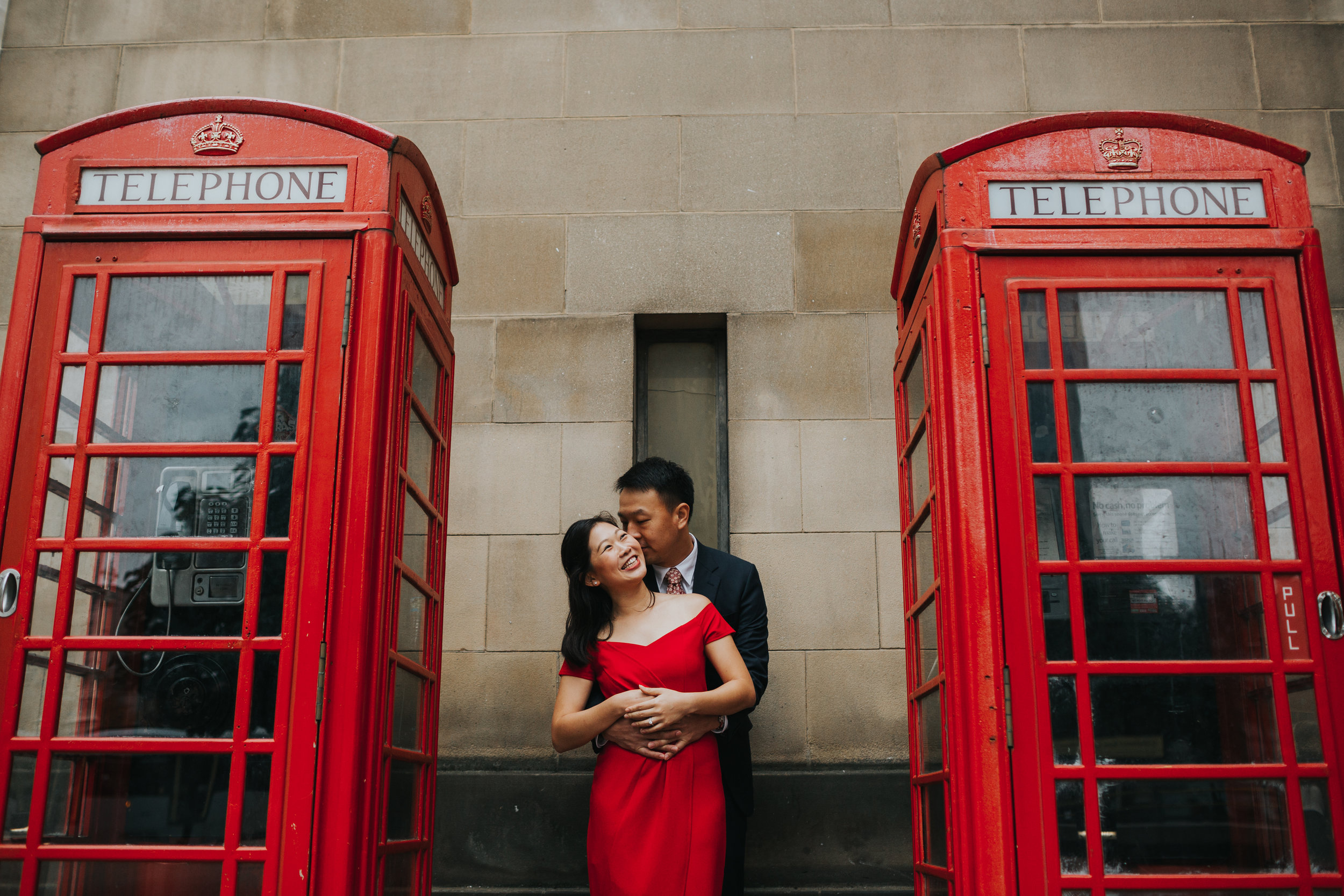 Couple in between two red phone boxes in Manchester.