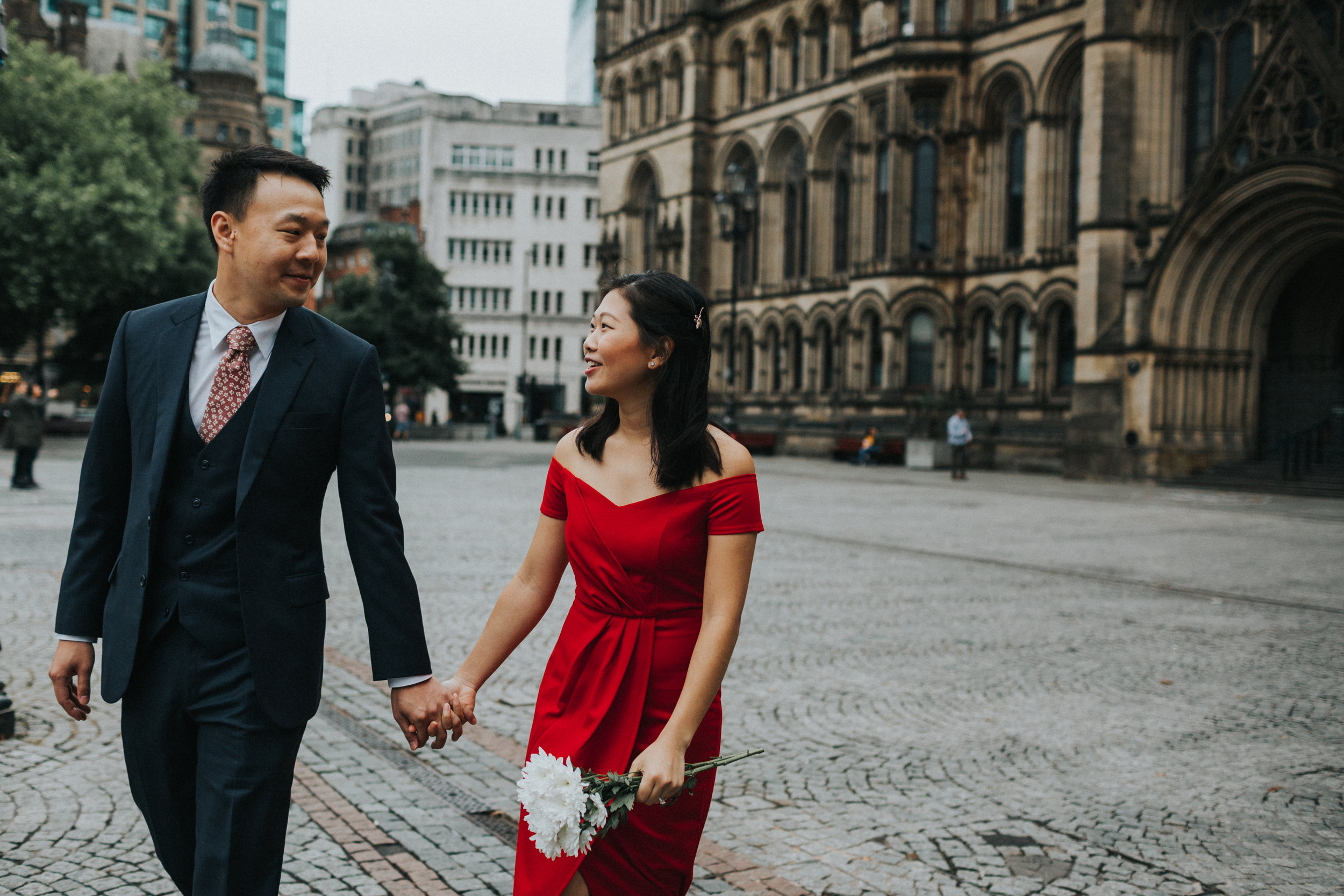 Couple walking together in front of Manchester Town Hall.