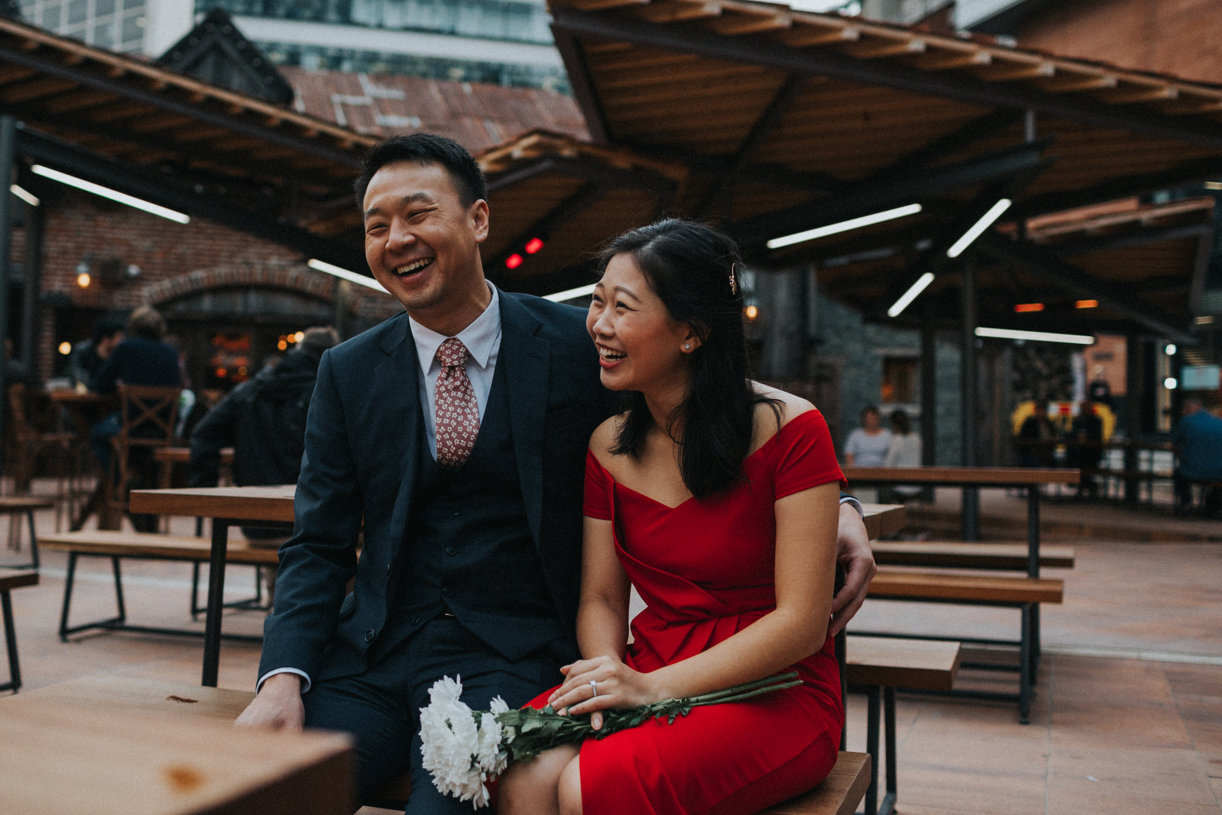 Couple sit and laugh together.