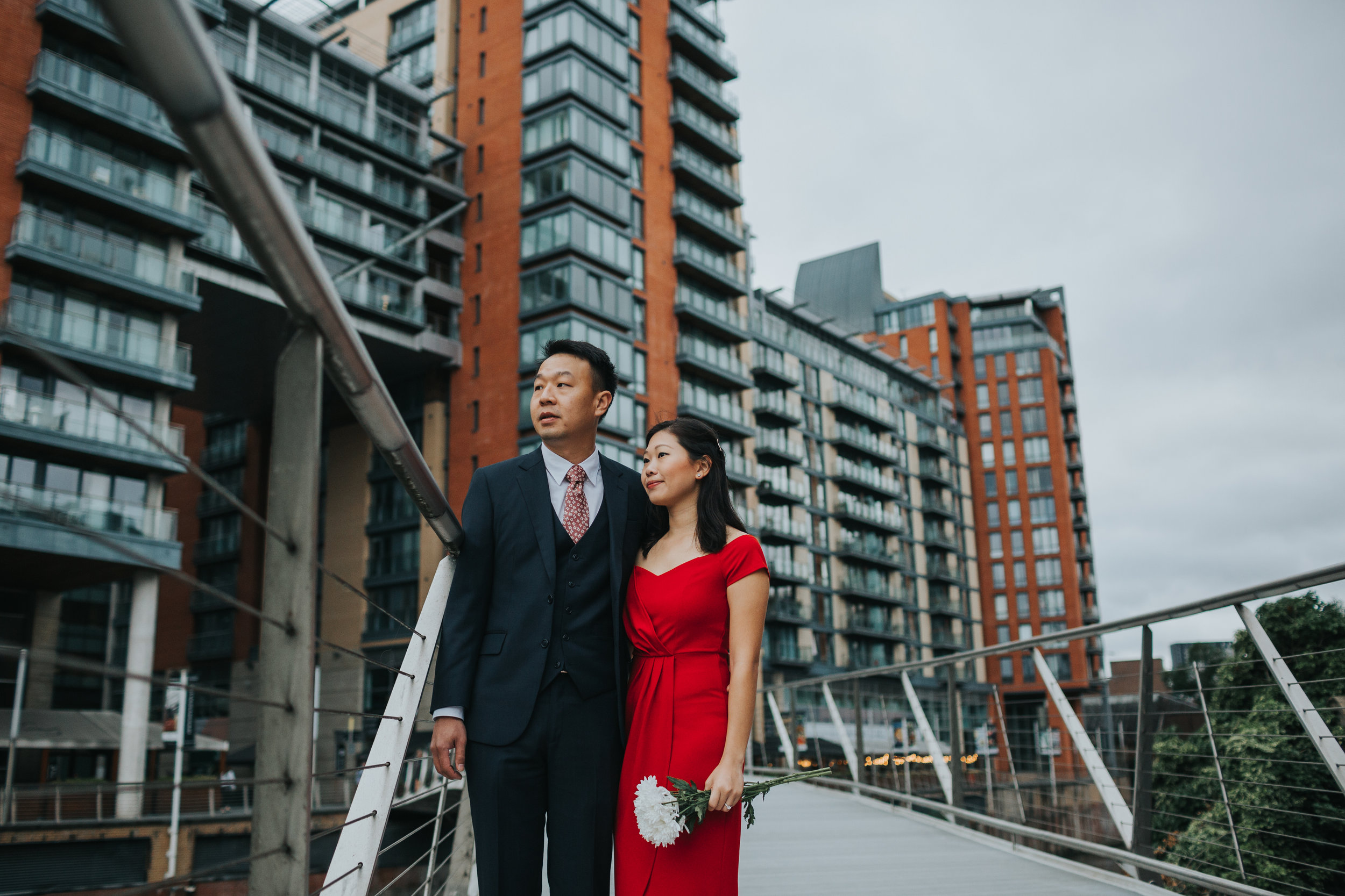 Couple stand outside Max's old University Halls on a bridge looking off into the distance.