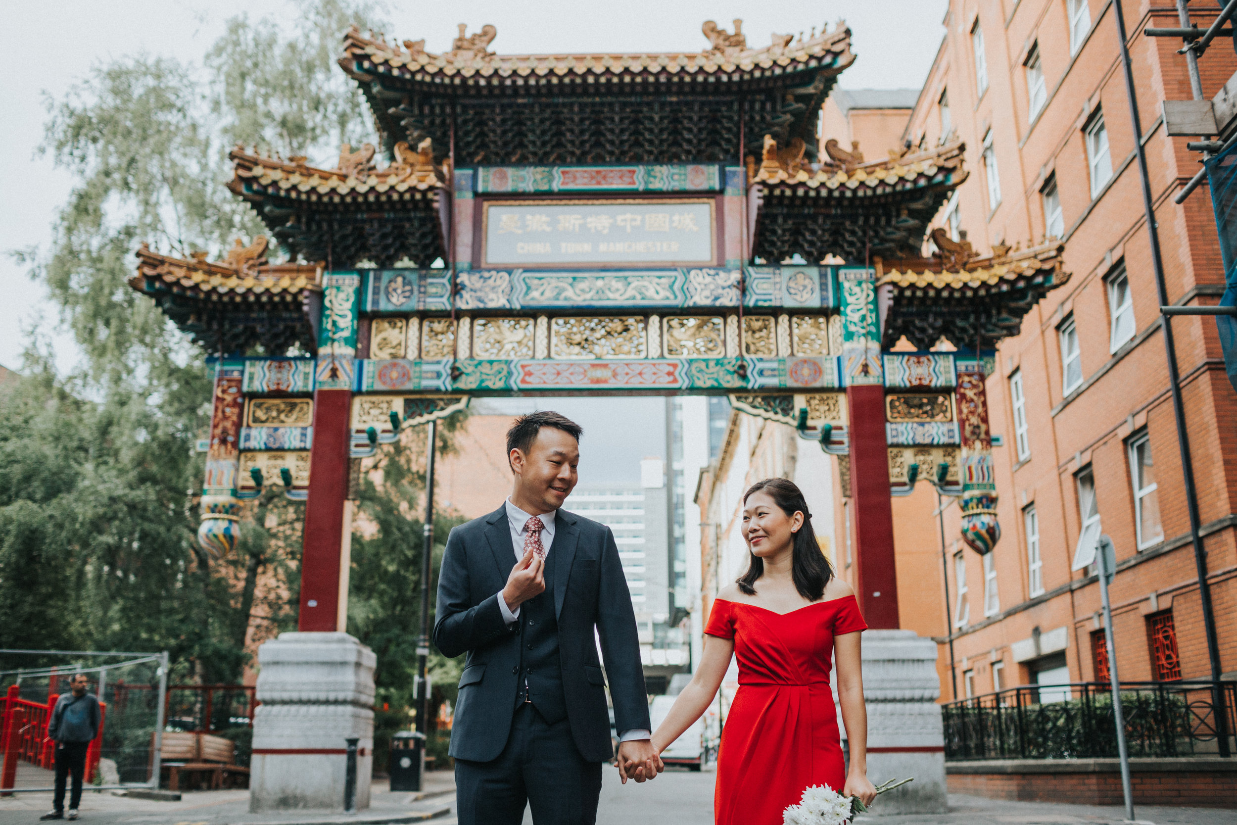 Couple stand under China Town Archway together.