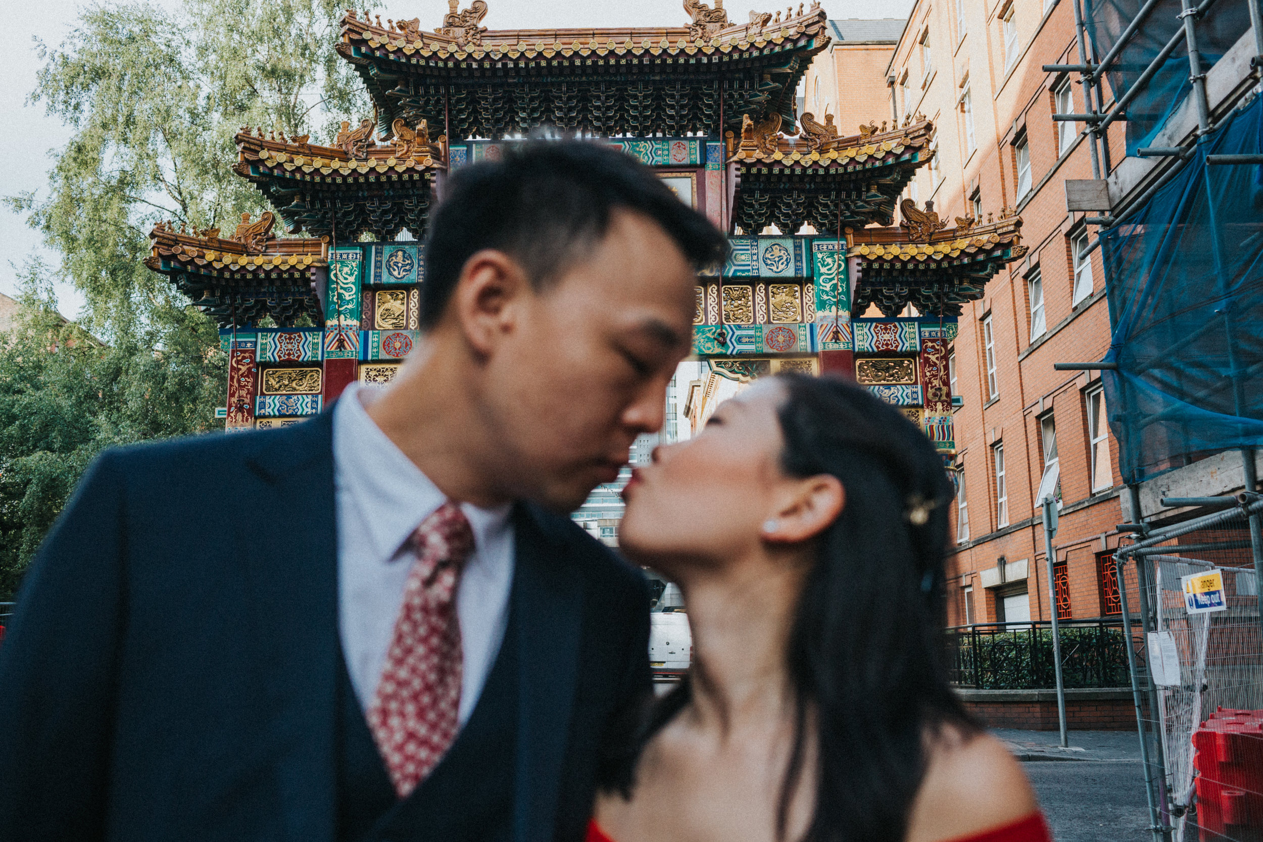 Couple kiss under China Town Archway. Focus on arch.