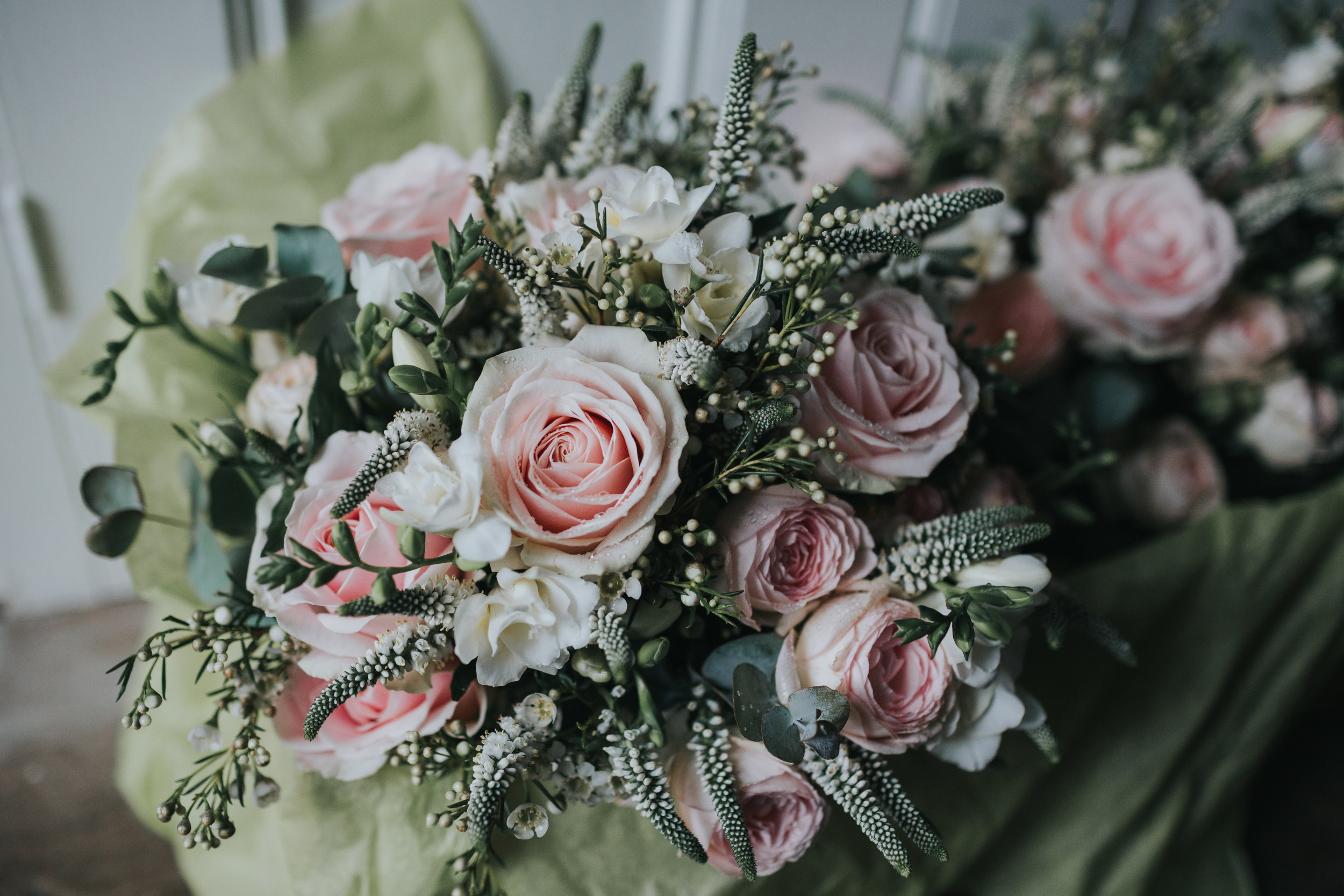Brides bouquet, pink flowers and pale green leaves.