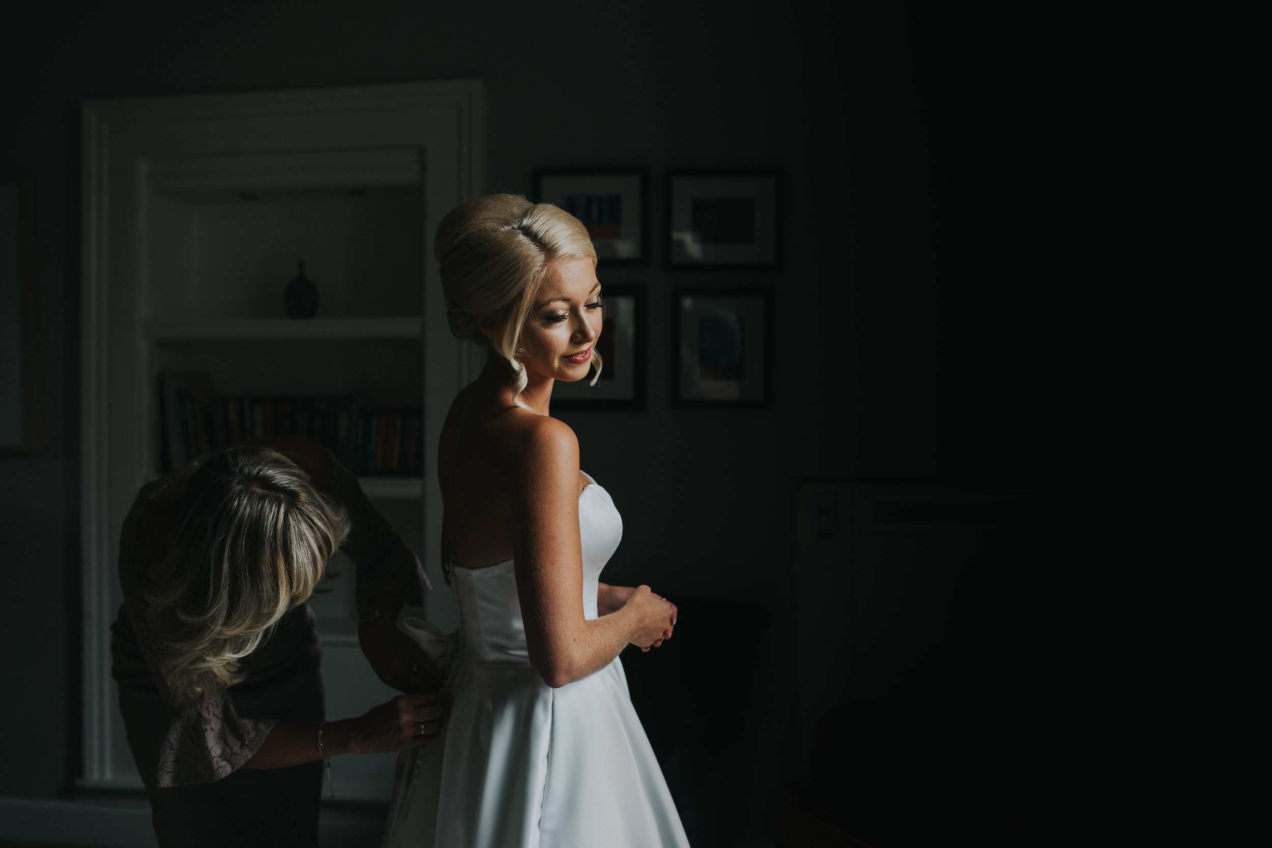 The bride stands in window light as her mother helps her put on her dress.