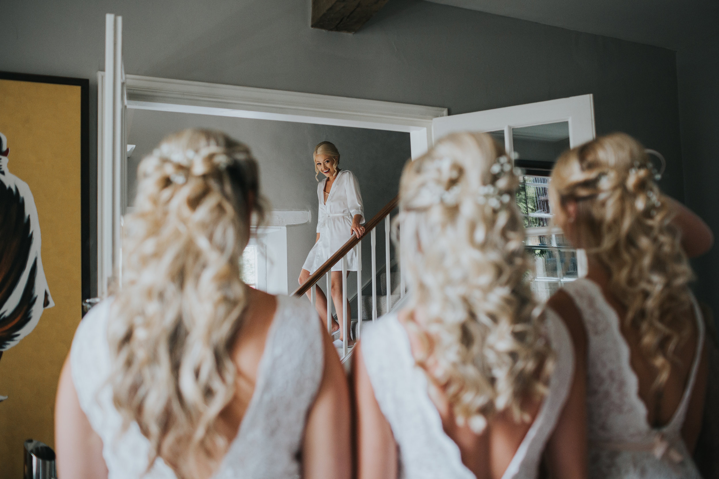 Bride comes down to see her bridesmaids in their dresses for the first time.