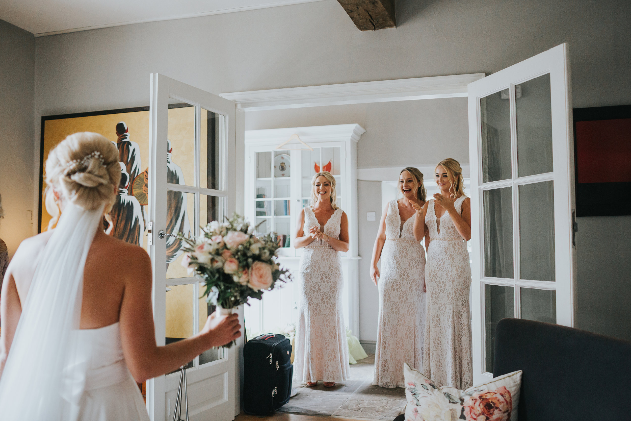Bridesmaids see Bride in her wedding dress for the first time.