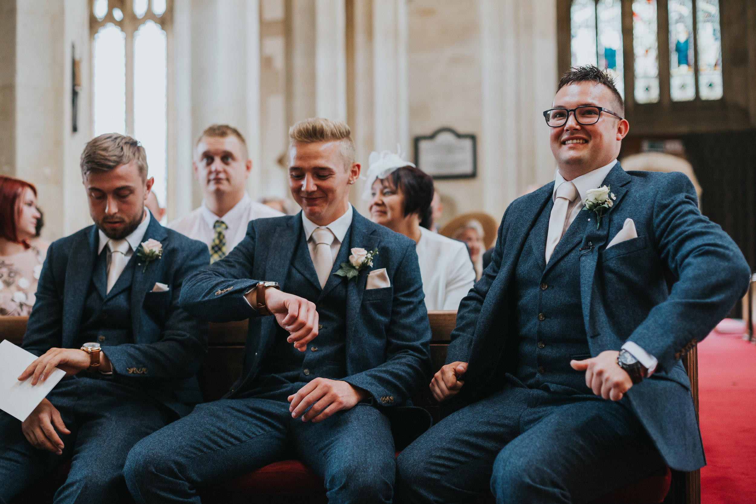 Groom waits inside the church with his groomsmen. Best Man looking at his watch.