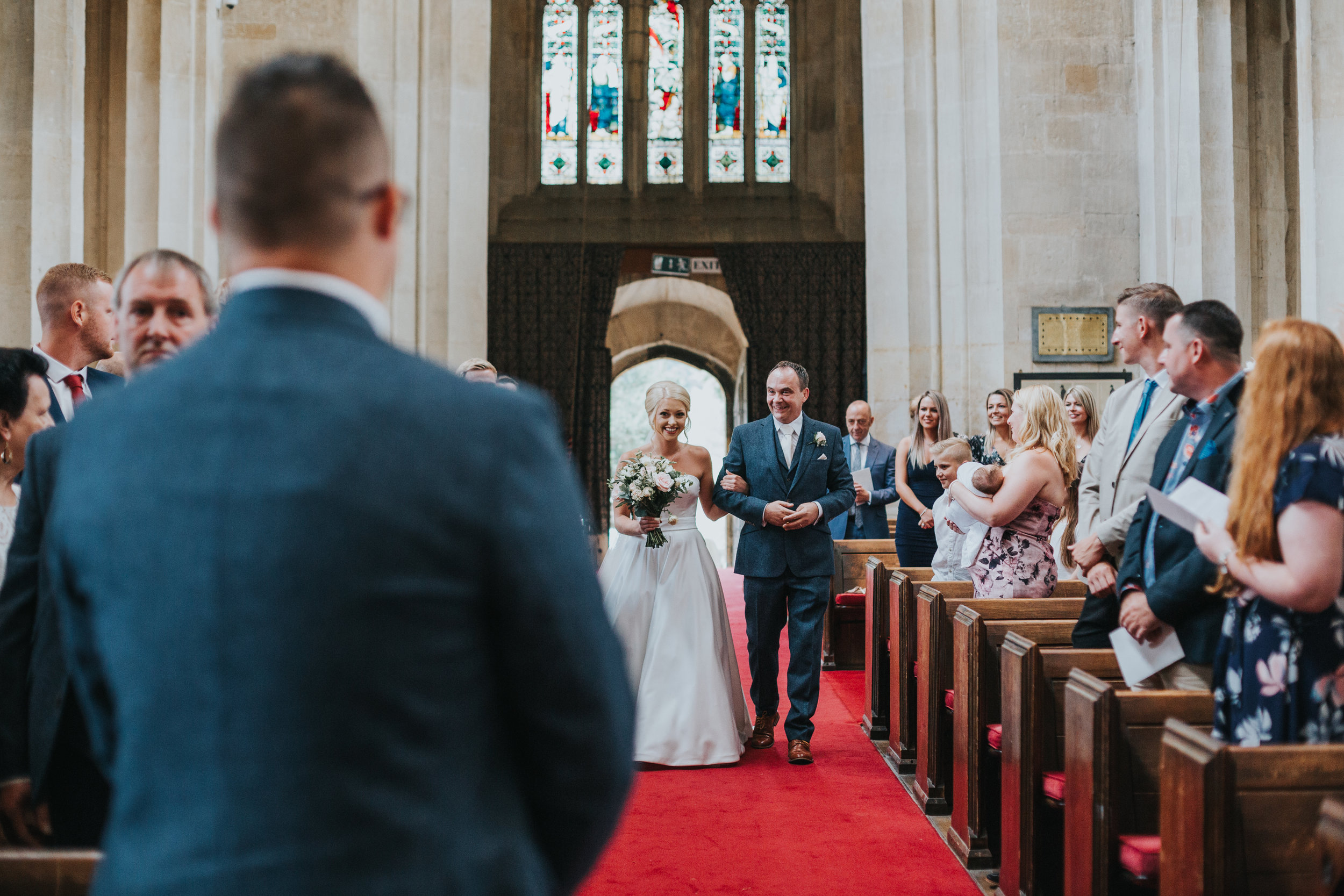 Bride and Father of the Bride walking down the aisle in St James Church in Chipping, Campden.