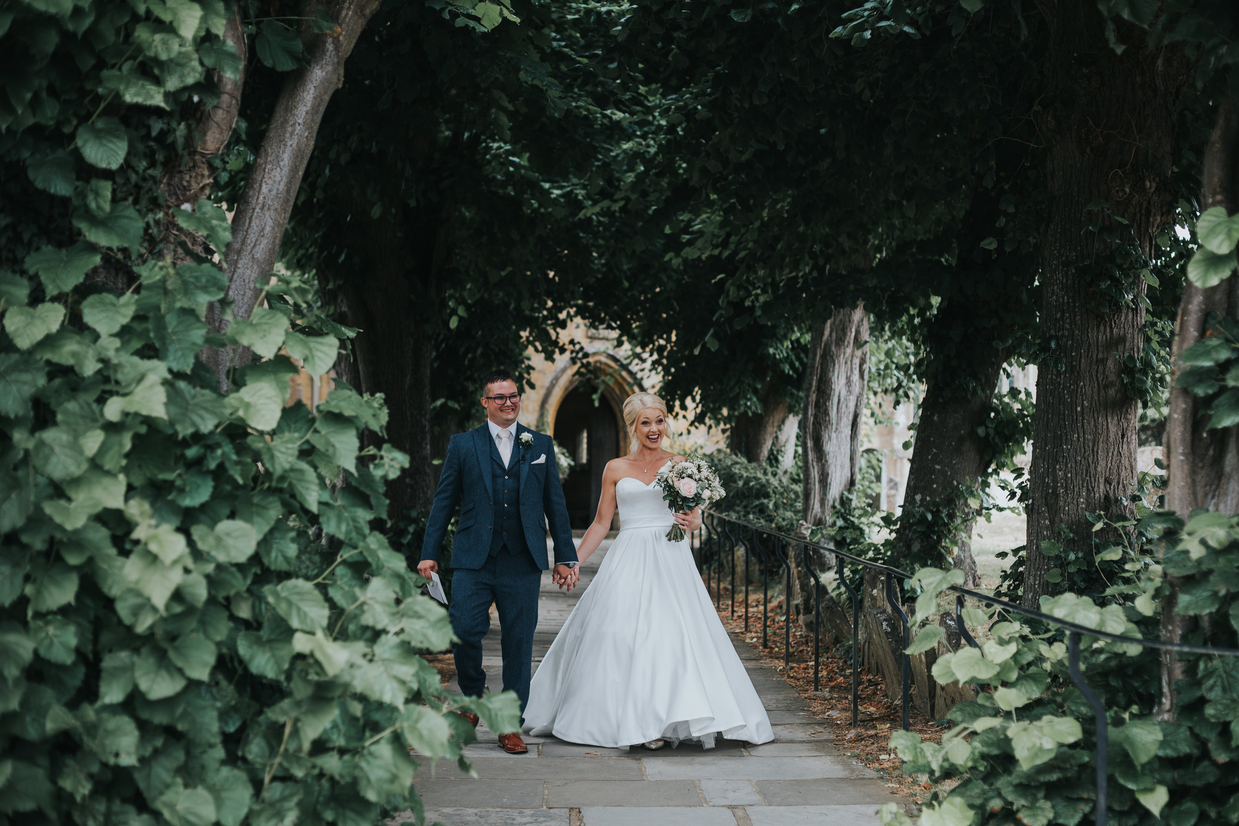 Bride and Groom walk down the church path towards their guests.
