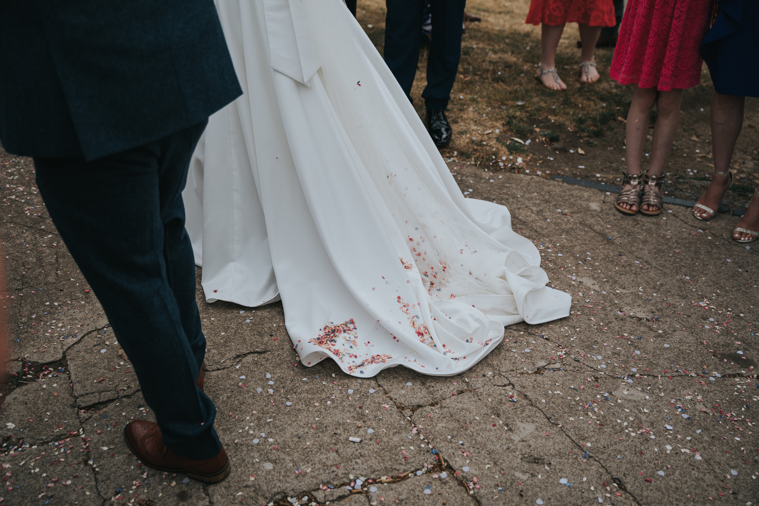 Confetti on brides dress.